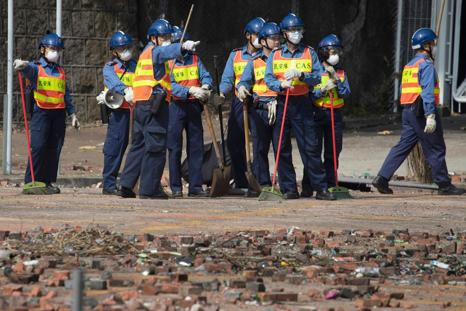 Workers start to clean up the road outside the Hong Kong Polytechnic University in Hong Kong on Wednesday, Nov. 20, 2019. (AP Photo/Ng Han Guan)