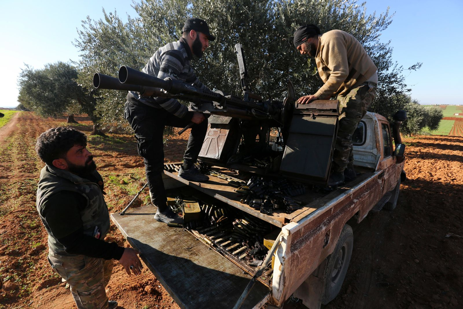 Turkish backed Syrian fighters load ammunition at a frontline near the town of Saraqib in Idlib province, Syria, Wednesday, Feb. 26, 2020. (AP Photo/Ghaith Alsayed)