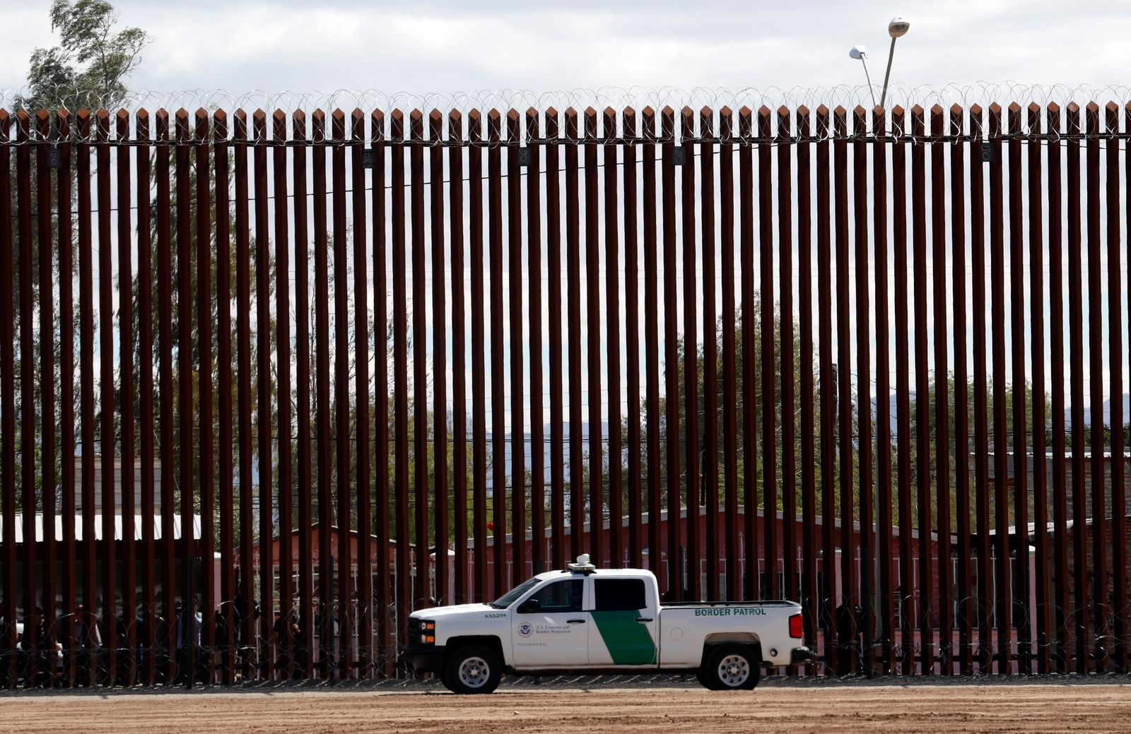 FILE - In this April 5, 2019, file photo, a U.S. Customs and Border Protection vehicle sits near the wall as President Donald Trump visits a new section of the border wall with Mexico in El Centro, Calif.{ } (AP Photo/Jacquelyn Martin, File)