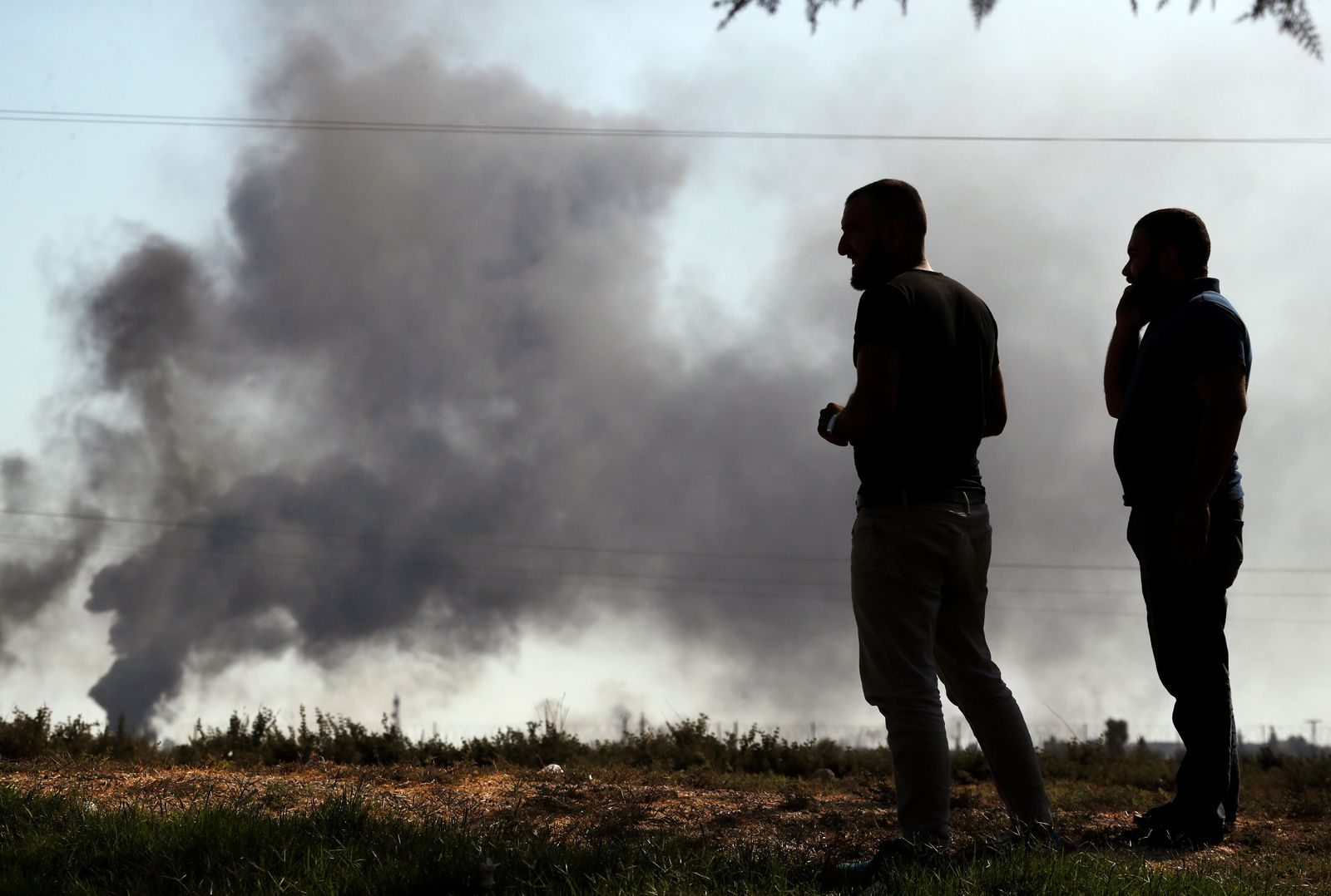 "People in Akcakale ,Sanliurfa province, southeastern Turkey, at the border with Syria, watch smoke billowing from targets inside Syria, during bombardment by Turkish forces, Thursday, Oct. 10, 2019. Turkey's foreign minister says Turkish troops intend to move some 30 kilometers (19 miles) deep into northern Syria and that its operation will last until all ""terrorists are neutralized,"" a reference to Syrian Kurdish fighters. (AP Photo/Lefteris Pitarakis)"