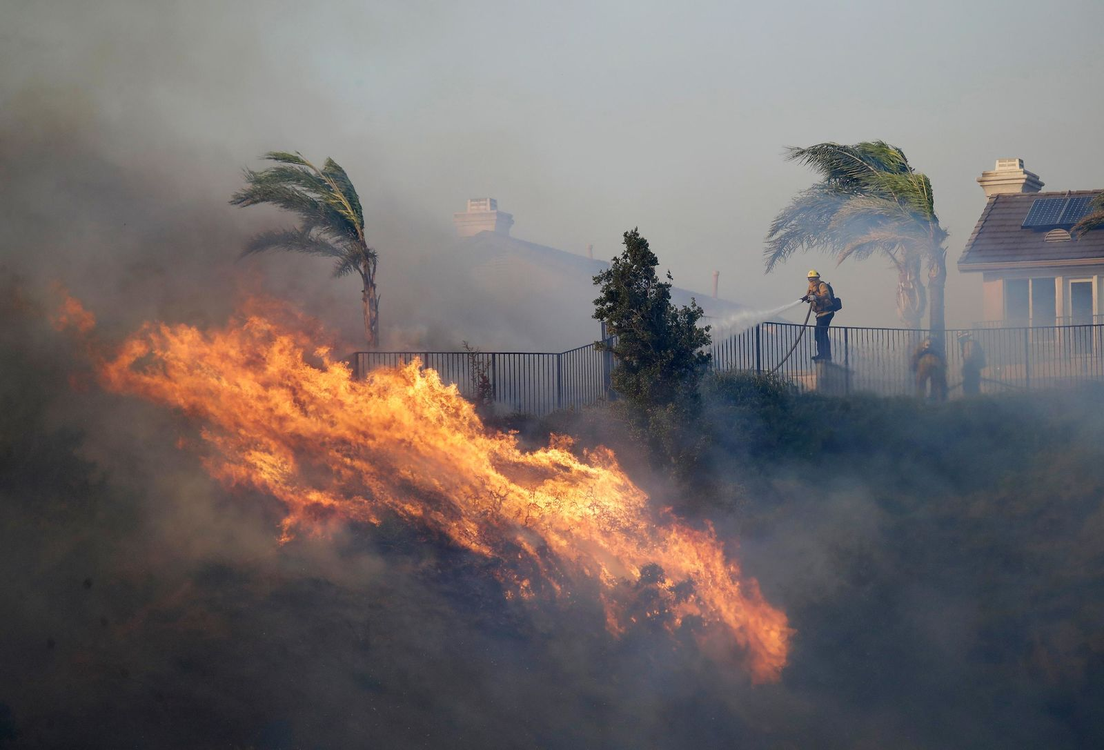 A firefighter sprays water in front of an advancing wildfire Friday, Oct. 11, 2019, in Porter Ranch, Calif. (AP Photo/Marcio Jose Sanchez)