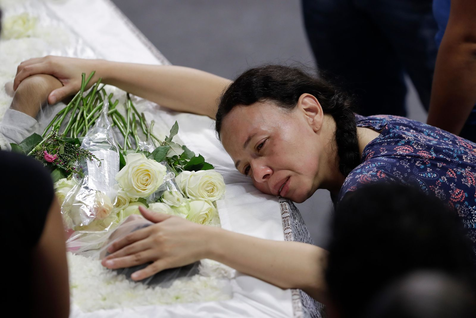 A relative mourns 15-year-old Caio Oliveira, a victim of a mass shooting at the Raul Brasil State School, in Suzano, Brazil, Thursday, March 14, 2019. (AP Photo/Andre Penner)