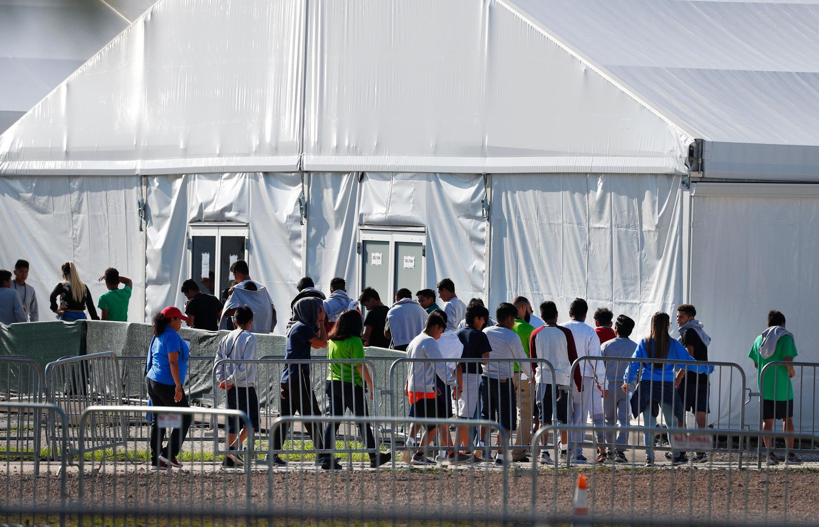 FILE- In this Feb. 19, 2019 file photo, children line up to enter a tent at the Homestead Temporary Shelter for Unaccompanied Children in Homestead, Fla. The American Civil Liberties Union is seeking potentially millions of dollars in damages on behalf of thousands of immigrant families who were separated at the U.S.-Mexico border. The ACLU and other attorneys filed a lawsuit Thursday, Oct. 3, 2019, against past and present Trump administration officials in federal court in Tucson alleging the government violated immigrants' rights and traumatized young children who were taken from their parents after crossing the border illegally. (AP Photo/Wilfredo Lee, File)