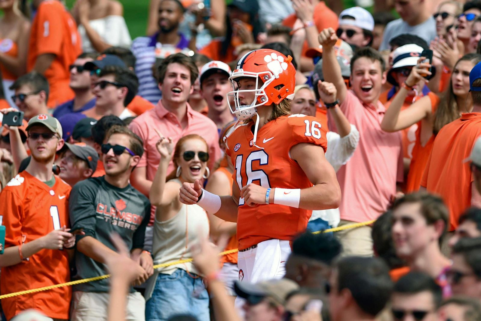 "FILE - In this Sept. 29, 2018, file photo, Clemson quarterback Trevor Lawrence runs down ""The Hill"" before the start of an NCAA college football game against Syracuse, in Clemson, S.C. For the first time, the defending national champion Tigers are No. 1 in The Associated Press preseason Top 25 presented by Regions Bank, Monday, Aug. 19, 2019. Clemson won its second national title in three seasons behind freshman quarterback Trevor Lawrence to claim equal standing with Alabama at the top of the sport. (AP Photo/Richard Shiro, File)"