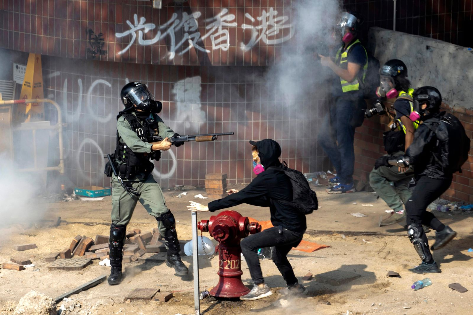 A policeman in riot gear points his weapon as protesters try to flee from the Hong Kong Polytechnic University in Hong Kong, Monday, Nov. 18, 2019.{ } (AP Photo/Ng Han Guan)
