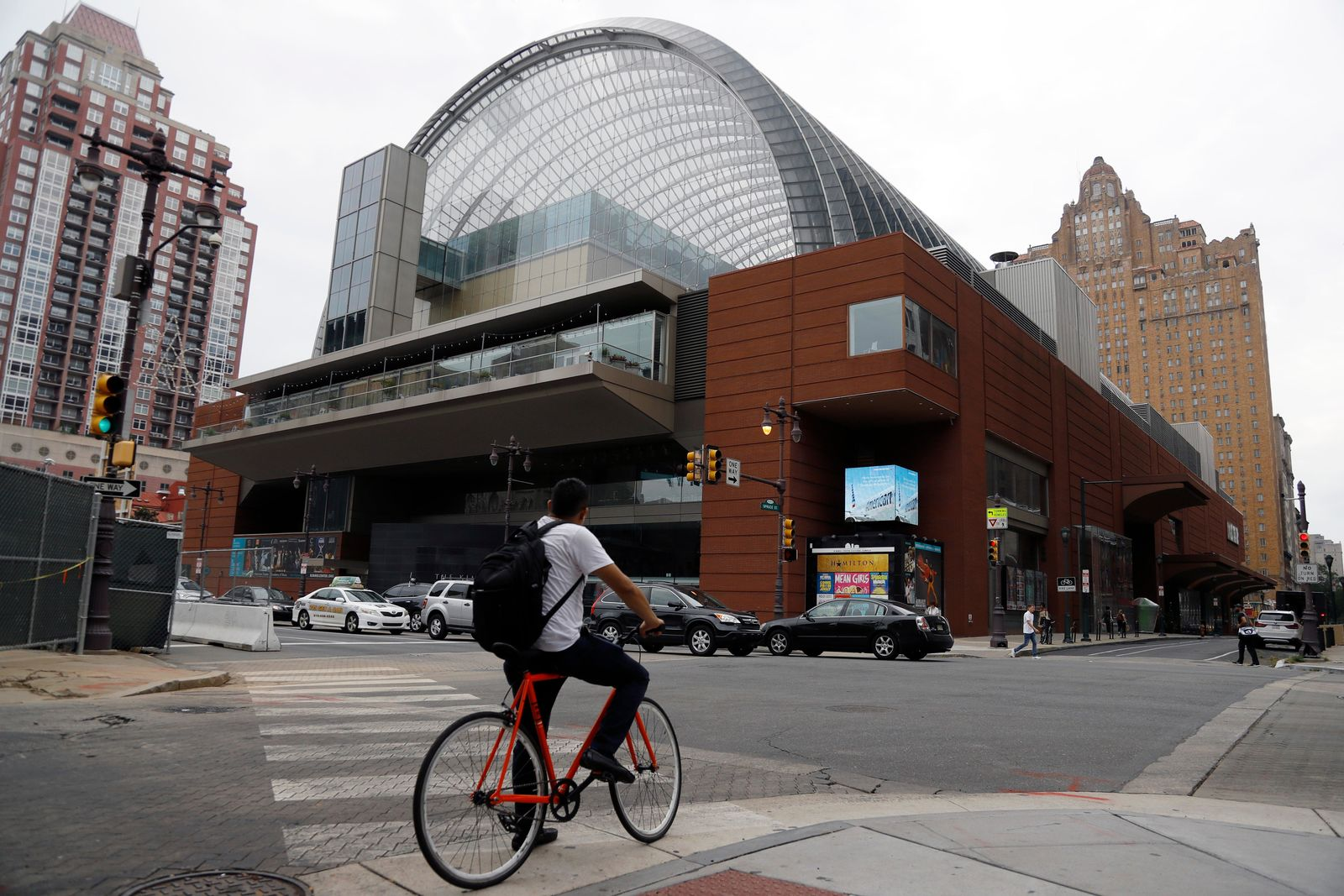 A cyclist passes by The Kimmel Center for the Performance Arts, Tuesday, Aug. 13, 2019, in Philadelphia.{ } (AP Photo/Matt Slocum)