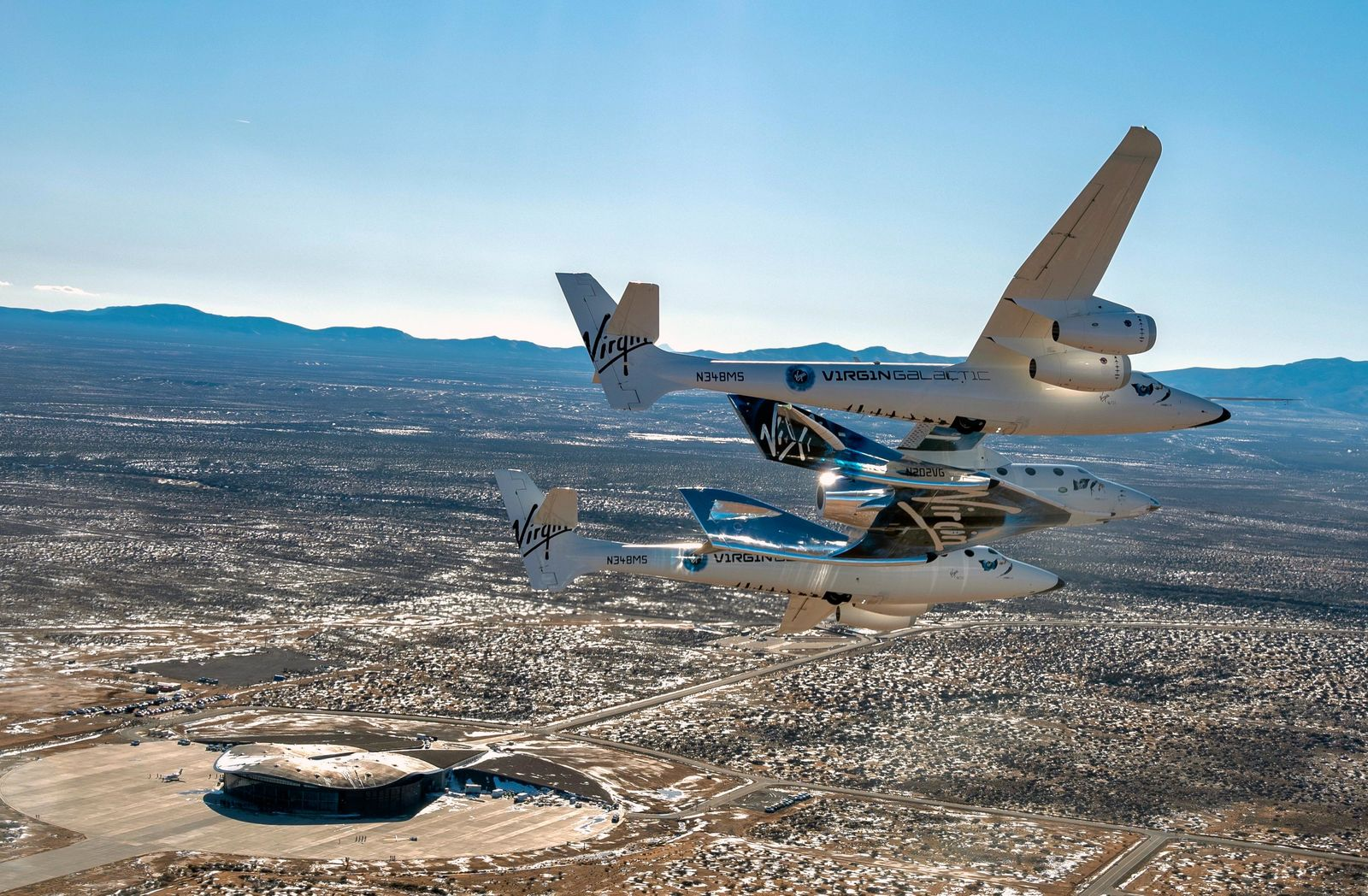 FILE - This Thursday, Feb. 13, 2020, file photo provided by Virgin Galactic shows the Virgin Galactic's VSS Unity flying over Spaceport America in Truth or Consequences, N.M. Virgin Galactic has received nearly 8,000 online reservations of interest since its first successful test flight into space 14 months ago, the company said Tuesday, Feb. 25, 2020, as it nears commercial operation and prepares to reopen ticket sales. (Virgin Galactic via AP, File)