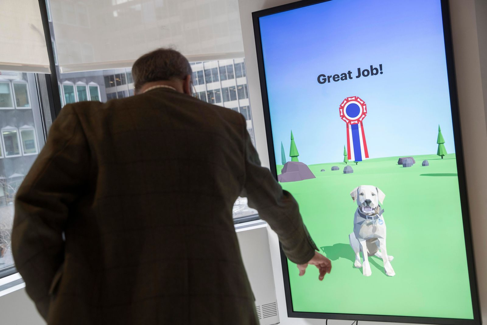 This Wednesday, Jan. 9, 2019, photo shows American Kennel Club Museum of the Dog's Executive Director Alan Fausel demonstrating the Basic Dog Training interactive kiosk with a virtual puppy during a tour of the museum in New York. The museum opens Feb. 8. (AP Photo/Mary Altaffer)