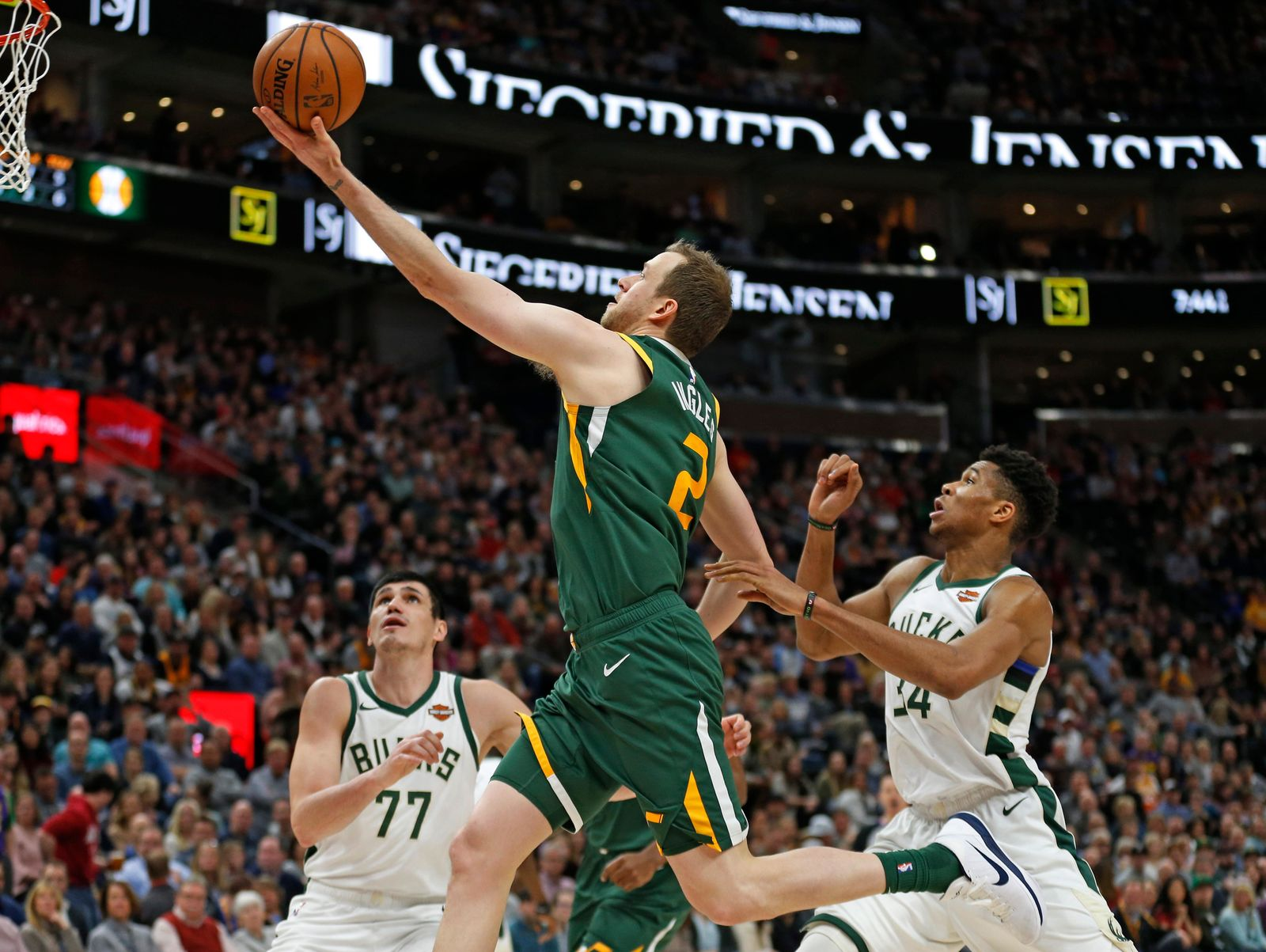 Utah Jazz forward Joe Ingles (2) goes to the basket as Milwaukee Bucks' Ersan Ilyasova (77) and Giannis Antetokounmpo (34) defend during the first half of an NBA basketball game Saturday, March 2, 2019, in Salt Lake City. (AP Photo/Rick Bowmer)