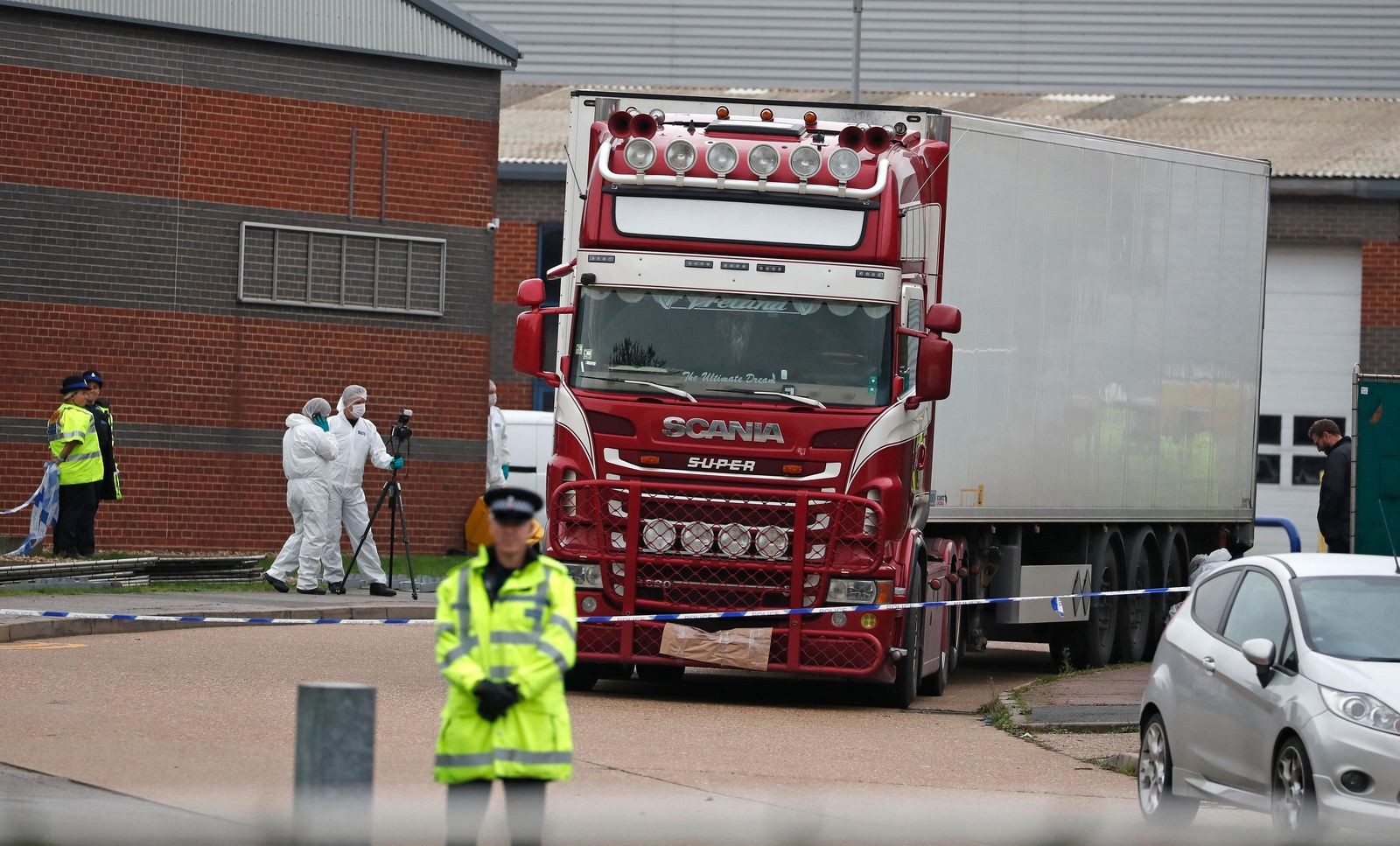 FILE - In this Oct. 23, 2019, file photo, police forensic officers attend the scene after a truck was found to contain a large number of dead bodies, in Thurrock, South England.{ } (AP Photo/Alastair Grant, File)