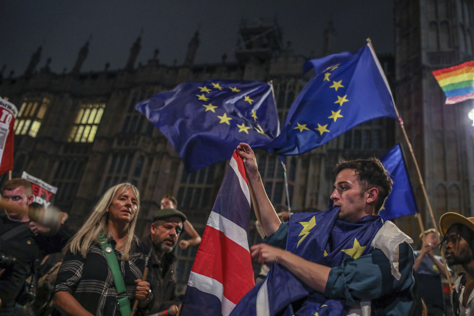Protesters outside the House of Commons, London, Tuesday, Sept. 3, 2019. British Prime Minister Boris Johnson suffered key defections from his party Tuesday, losing a working majority in Parliament and weakening his position as he tried to prevent lawmakers from blocking his Brexit plans. (AP Photo/Vudi Xhymshiti)