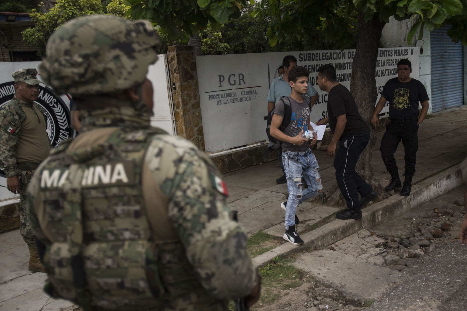 A man without legal permission to be in Mexico leaves an office of the Attorney General before being sent to Tapachula in an immigration van, as members of the National Guard stand watch in Arriaga, Mexico, Sunday, June 23, 2019. Mexico has completed its deployment of 6,000 National Guard agents to help control the flow of migrants headed toward the U.S. and filled  immigration agency posts to regulate border crossings, the government said Friday. (AP Photo/Oliver de Ros)