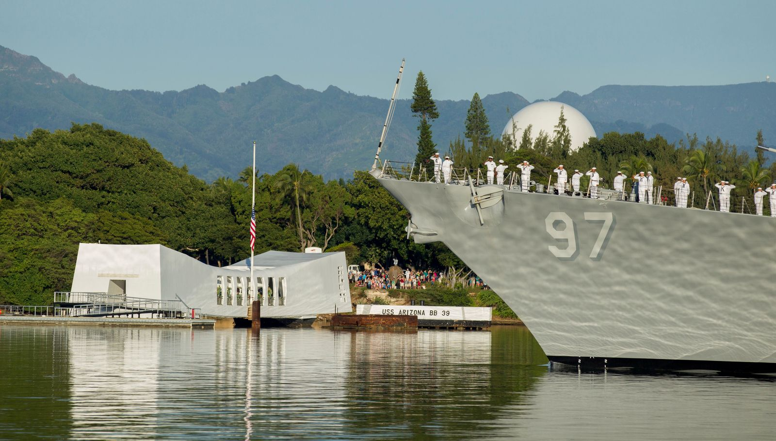FILE - In this Dec. 7, 2016, file photo, sailors on the USS Halsey salute while passing by the USS Arizona Memorial during a moment of silence at Pearl Harbor, Hawaii. Survivors and members of the public are expected to gather in Pearl Harbor on Saturday, Dec. 7, 2019, to remember those killed when Japanese planes bombed the Hawaii naval base 78 years ago and launched