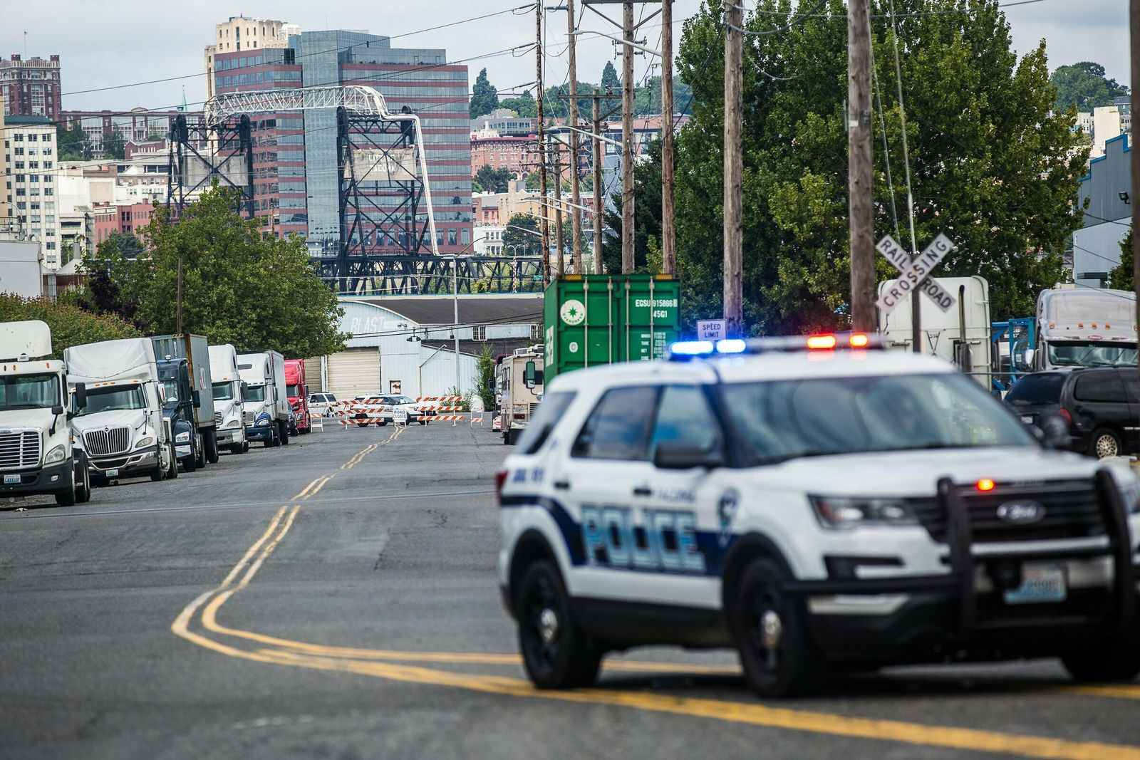 A police officer guards the front of a road block near the Northwest Detention Center, Saturday, July 13, 2019 in Tacoma, Wash. (Rebekah Welch/The Seattle Times via AP)