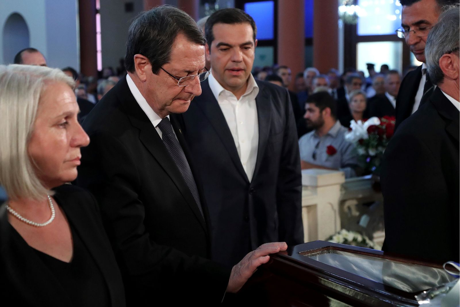 Cyprus' president Nicos Anastasiades, center, touches the coffin of the former Cyprus' President Dimitris Christofias as Greece's Prime minister Alexis Tsipras looks on, during Christofias' state funeral at the Orthodox Christian Church of the Lord's Wisdom in capital Nicosia, Cyprus, Tuesday, June 25, 2019.{ } (AP Photo/Petros Karadjias)