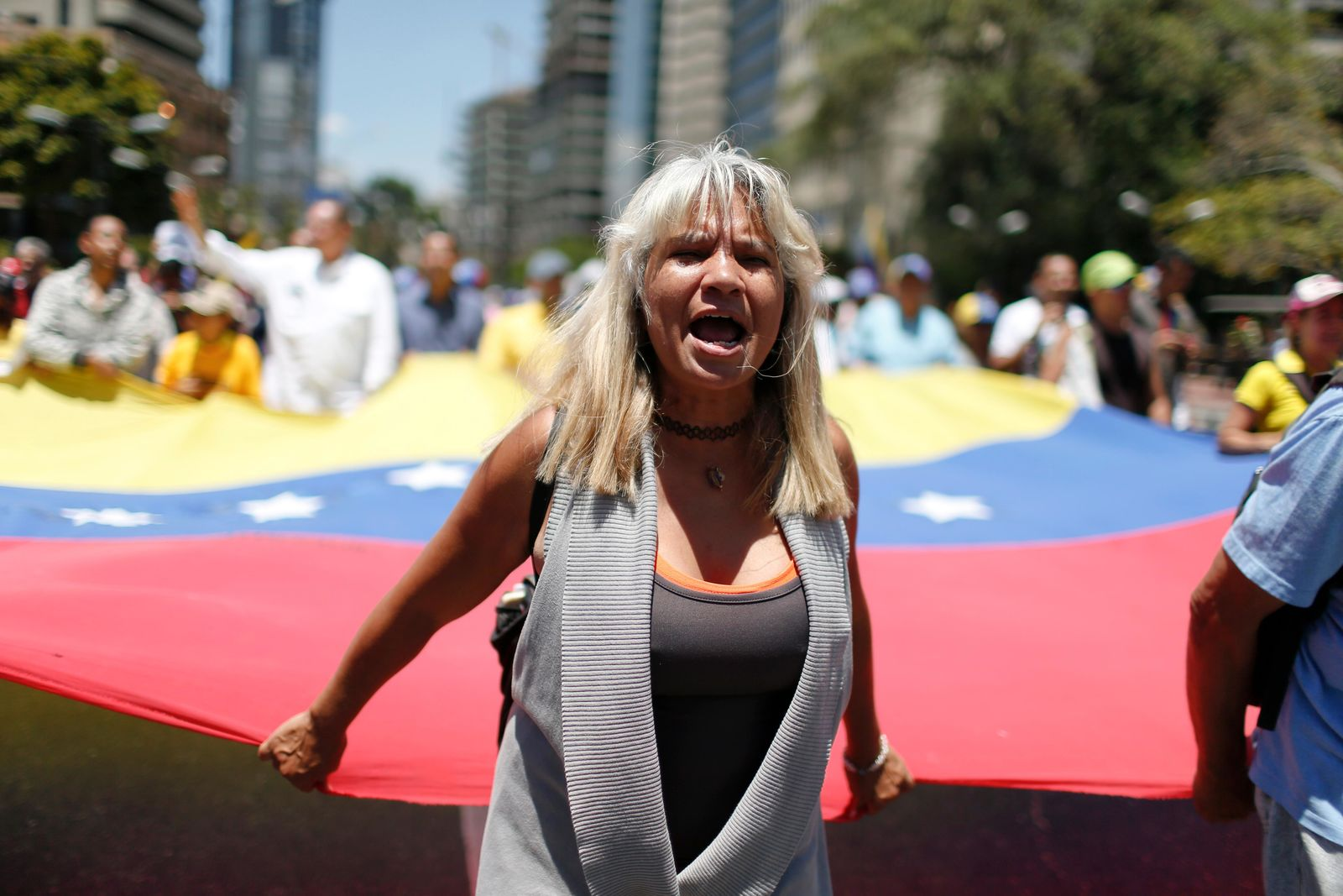 A supporter of opposition leader and self-proclaimed interim president Juan Guaido marches to protest outages that left most of the country scrambling for days in the dark in Caracas, Venezuela, Saturday, April 6, 2019. (AP Photo/Natacha Pisarenko)