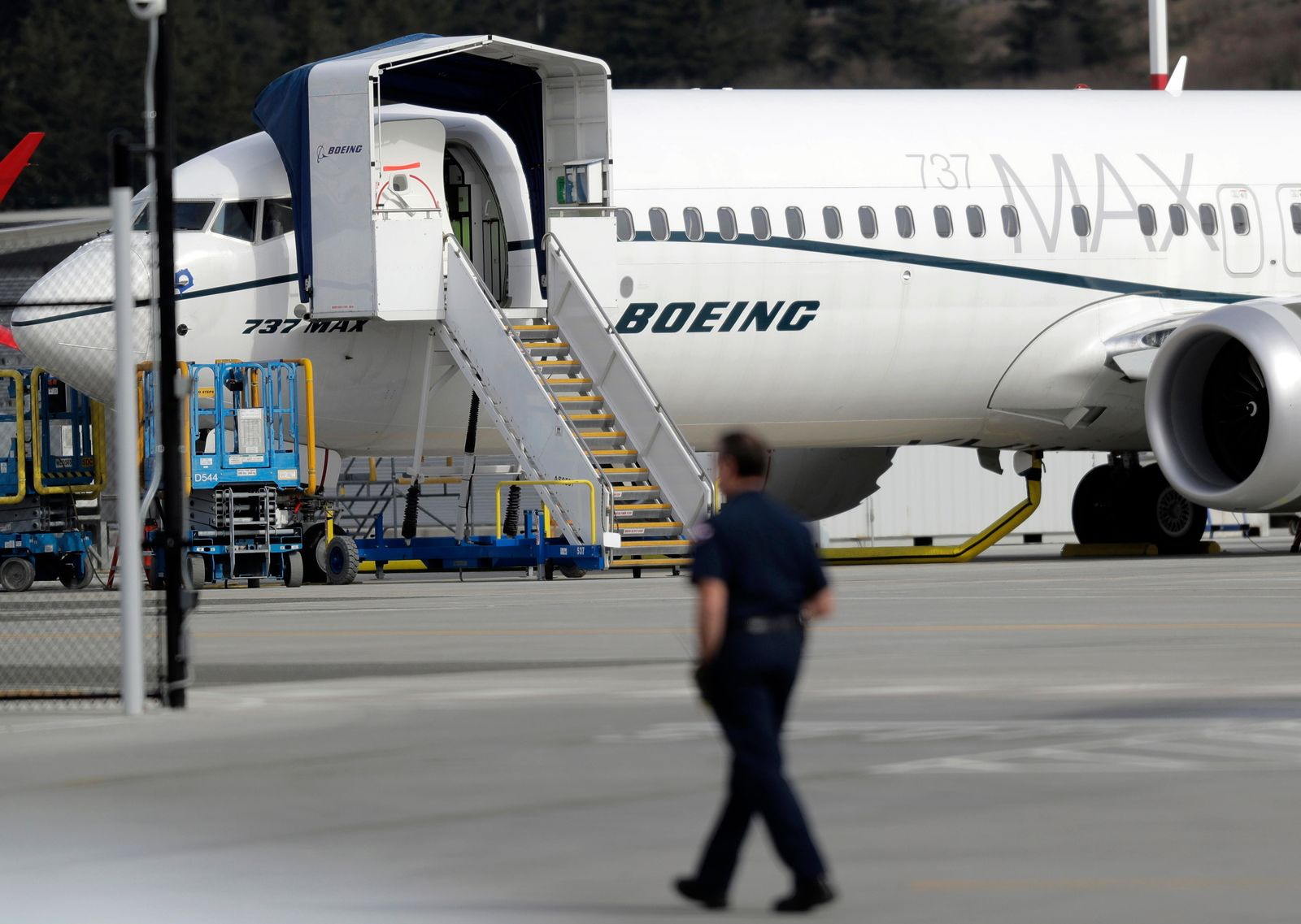 FILE- In this March 14, 2019, file photo a worker walks next to a Boeing 737 MAX 8 airplane parked at Boeing Field in Seattle.{ } (AP Photo/Ted S. Warren, File)
