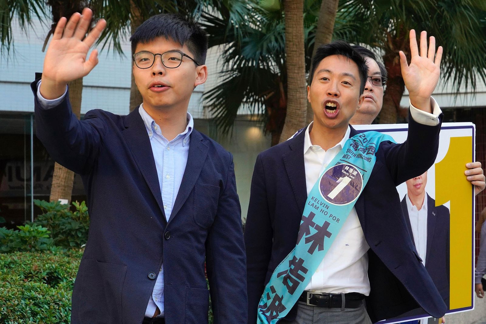 "Pro-democracy activist Joshua Wong, left, campaigns with local election candidate Kelvin Lam, right, in Hong Kong, Saturday, Nov. 23, 2019. Chanting ""No more tear gas,"" dozens of Hong Kong families with young children are marching to oppose the government's handling of protests on the eve of keenly contested local elections. (AP Photo/Vincent Yu)"