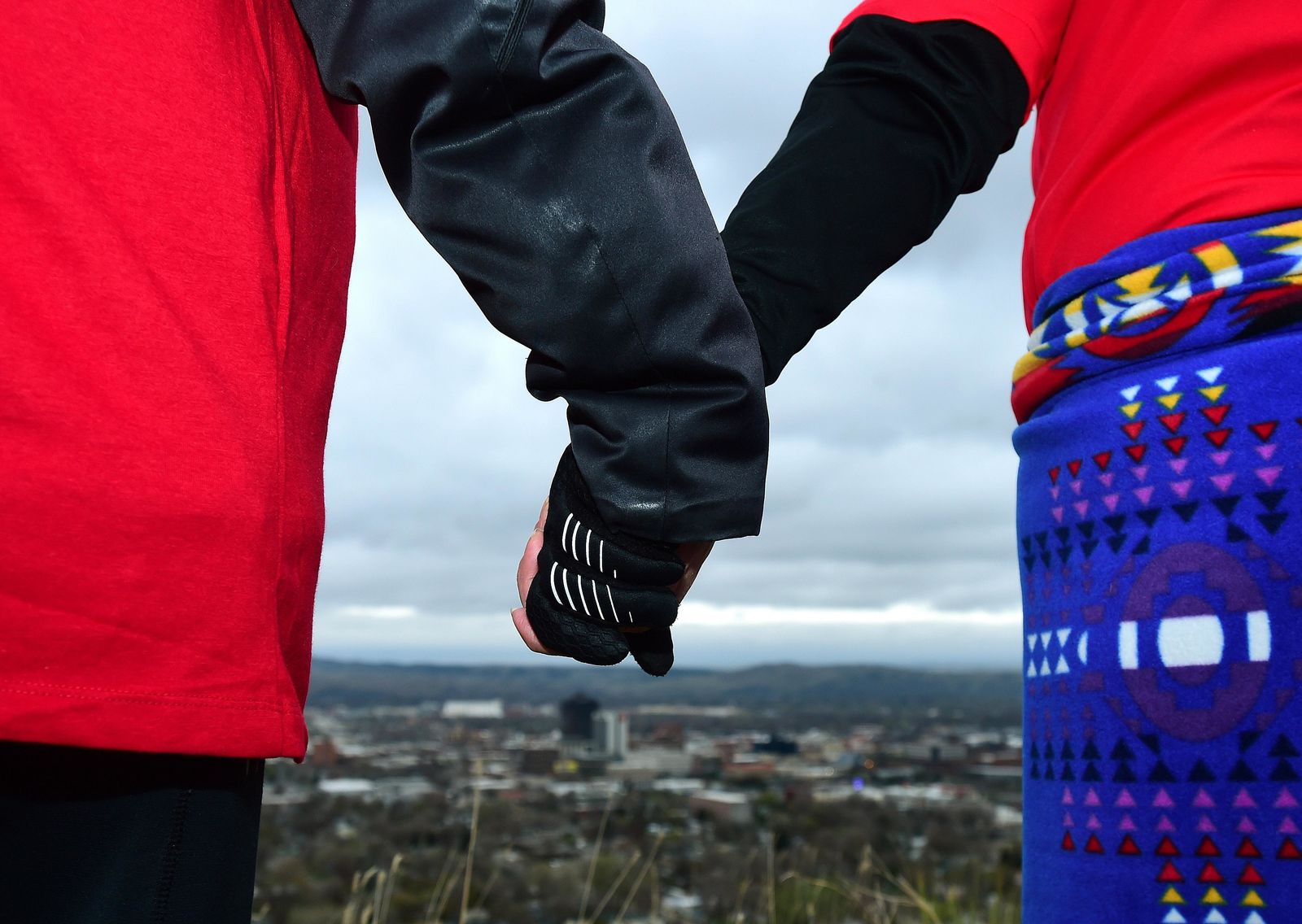 In this May 5, 2019, photo, hundreds hold hands as they form a line of the edge of the Billings Rimrocks for Line the Rims in Red event to honor missing and murdered indigenous people, in Billings, Mont. The event was organized by MSU Billings and community partners. Participants brought posters of men, women and children who are missing, and changed the name of the local movement to Missing and Murdered Indigenous People.  (Larry Mayer/The Billings Gazette via AP)