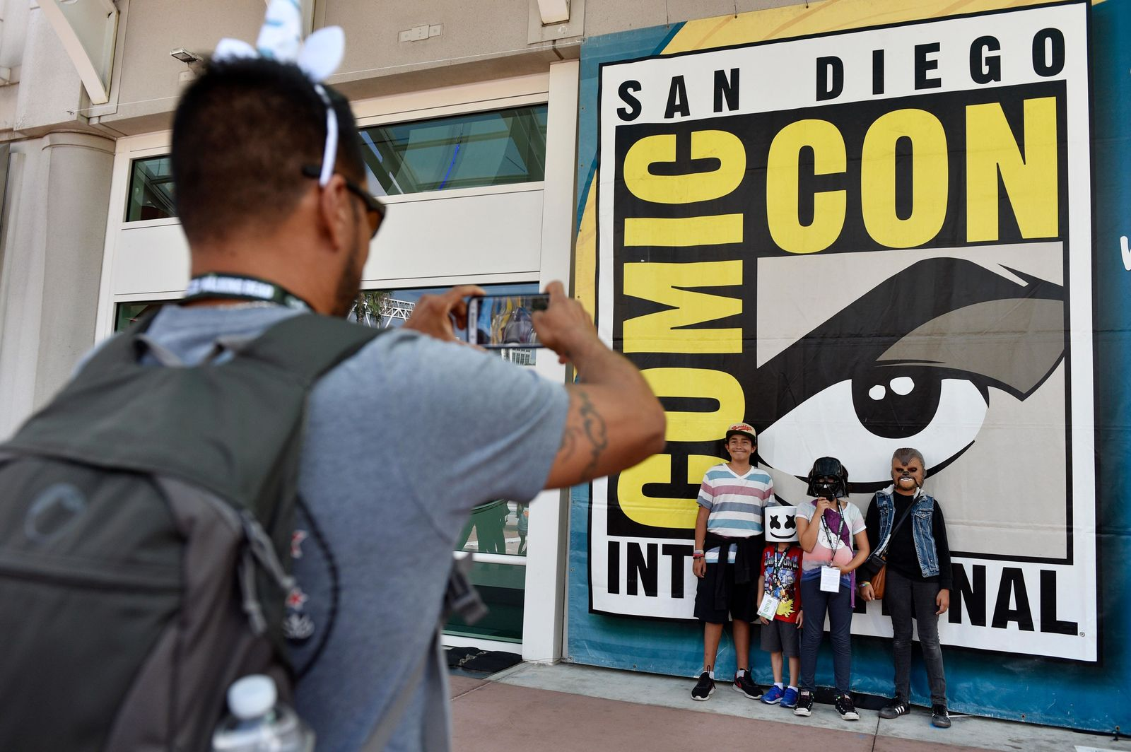 Luis Ramos, left, of San Diego takes a picture of his son Alek, 6, third from right, and daughter Anabel, 11, second from right, and their friends Emiliano Beltran, 12, fourth from right, and Isabel Beltran, 10, before Preview Night at the 2018 Comic-Con International at the San Diego Convention Center, Wednesday, July 18, 2018, in San Diego. (Photo by Chris Pizzello/Invision/AP)