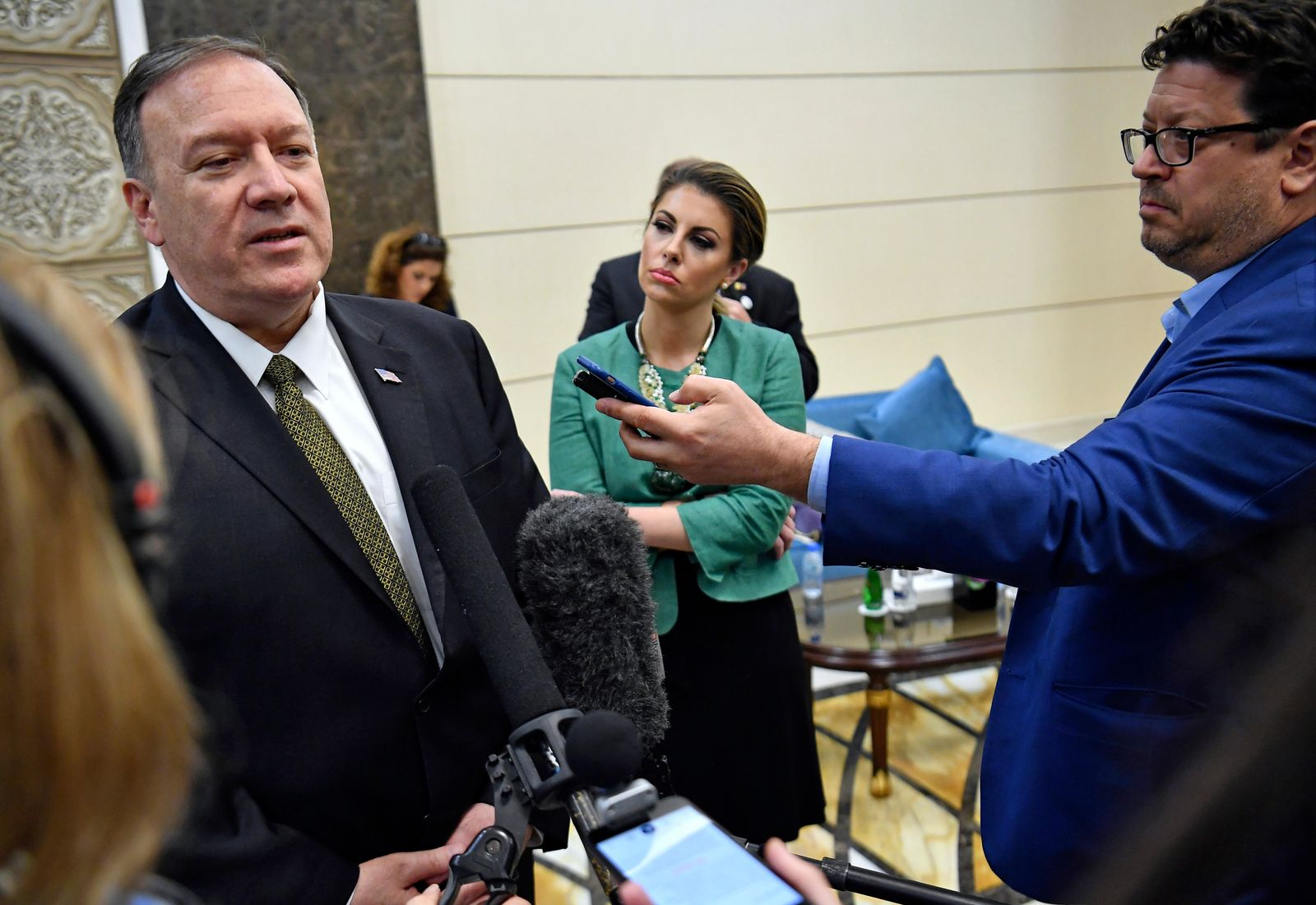 U.S. Secretary of State Mike Pompeo speaks to the media before departing from al-Bateen Air Base in Abu Dhabi, United Arab Emirates, Thursday, Sept. 19, 2019, as State Department spokesperson Morgan Ortagus, second from right, listens. (Mandel Ngan/Pool via AP)