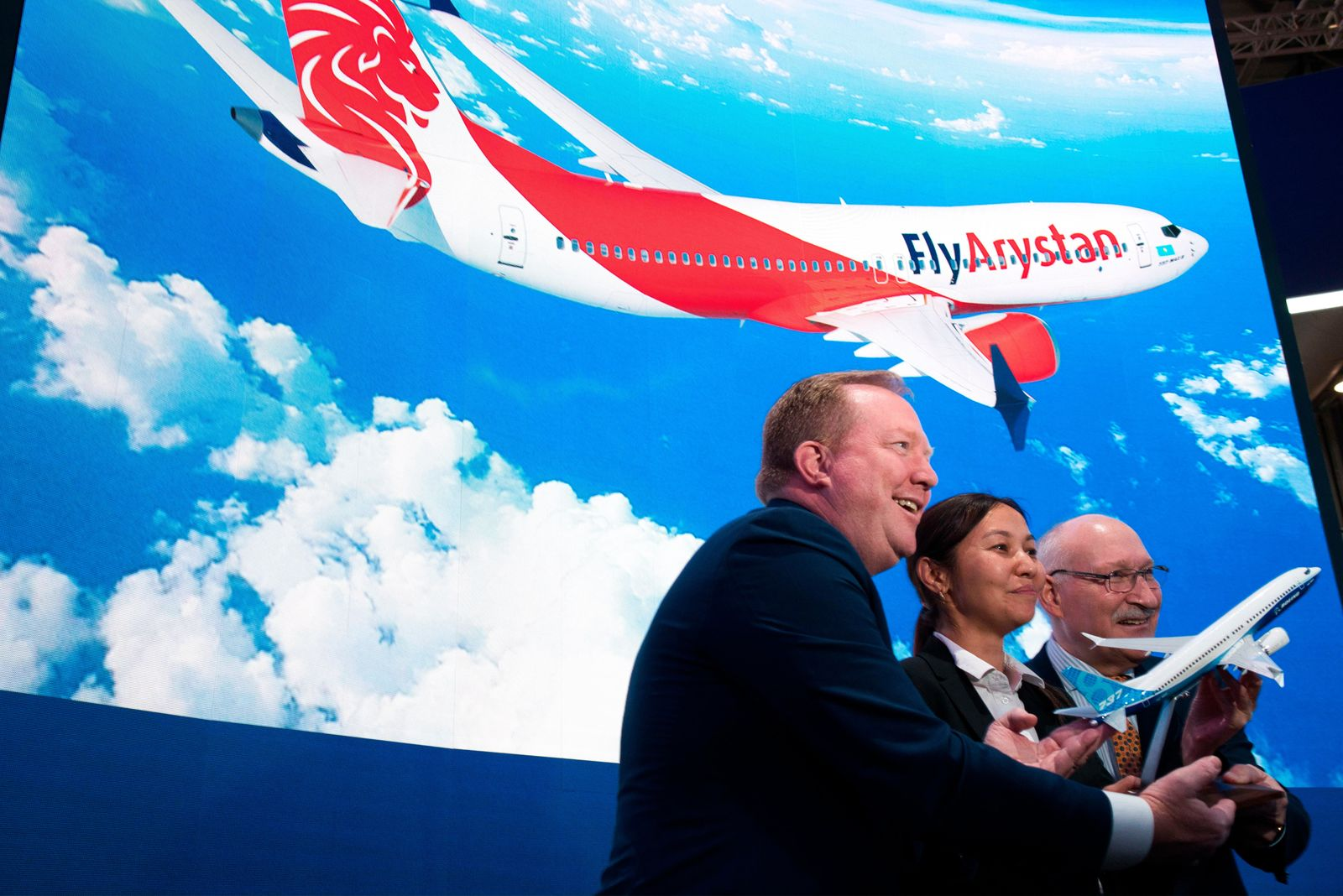 From left; Boeing Commercial Airplanes president and CEO Stanley A. Deal, Air Astana chief planning officer Alma Aliguzhinova and Air Astana chief operating officer Anthony Regan pose after a news conference at the Dubai Airshow in Dubai, United Arab Emirates, Tuesday, Nov. 19, 2019. (AP Photo/Jon Gambrell)