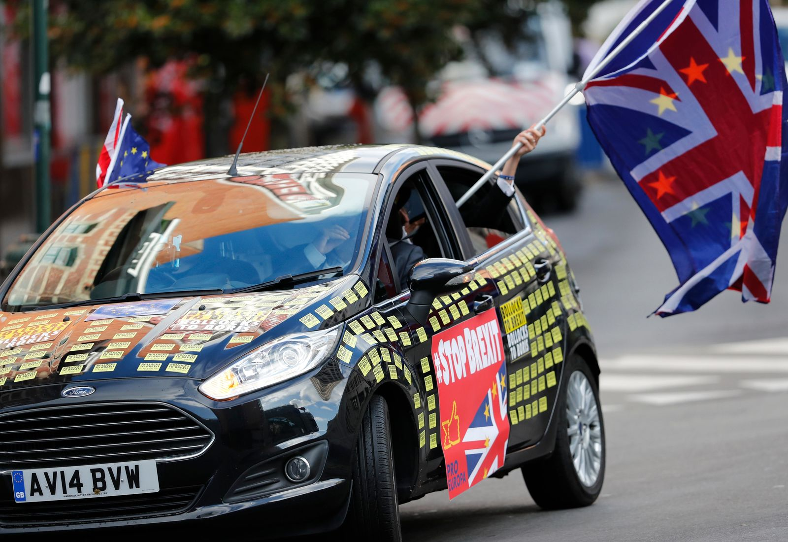 A man waves an EU and Union flag out of a car adorned with anti-Brexit decals in front of EU headquarters in Brussels, Thursday, Oct. 17, 2019.{ } (AP Photo/Frank Augstein)