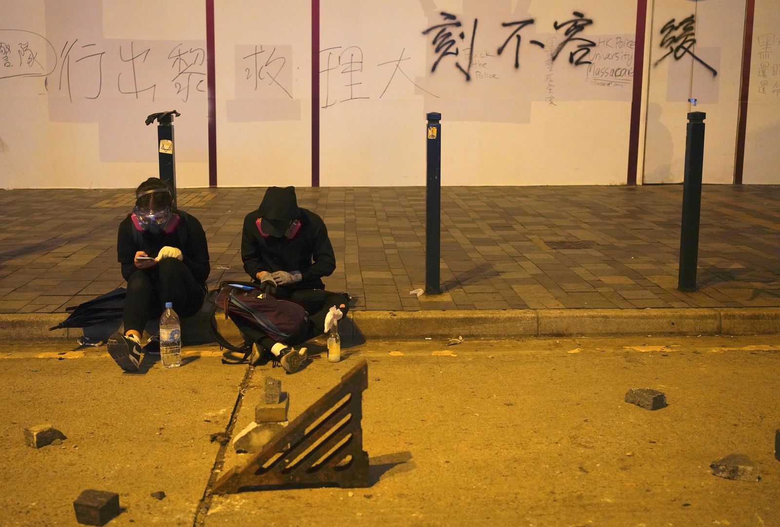 Protestors rest near a road barricaded with bricks in Hong Kong, early Tuesday, Nov. 19, 2019. (AP Photo/Vincent Yu)