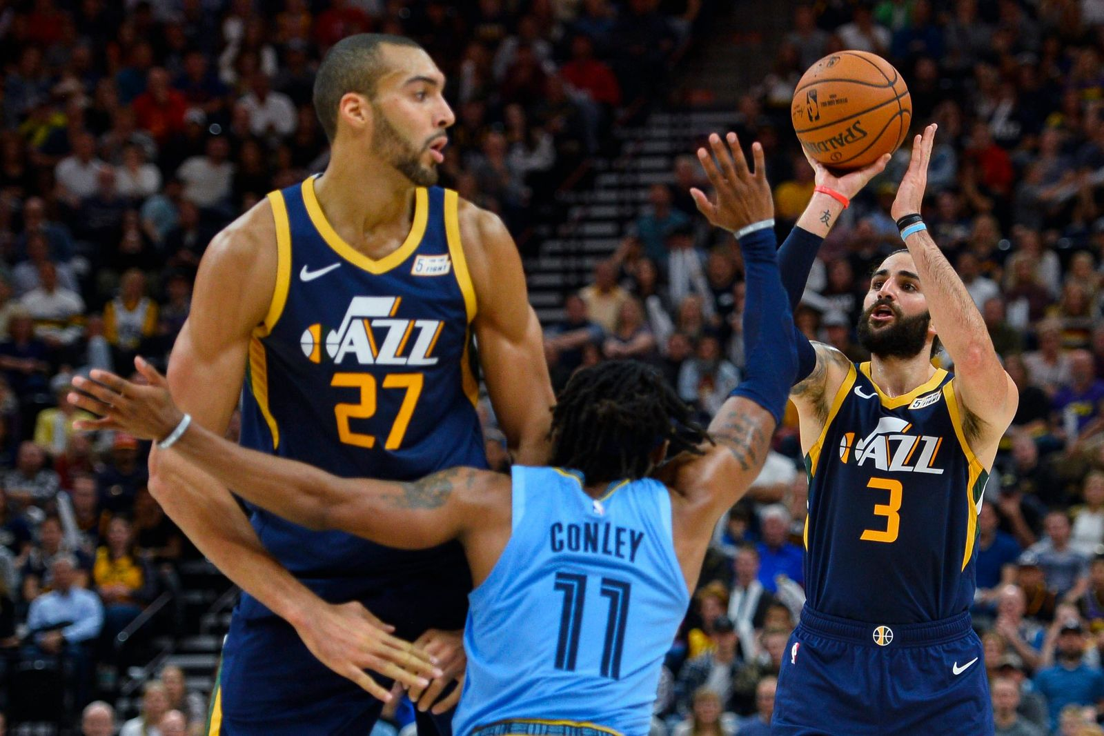 Utah Jazz guard Ricky Rubio (3) shoots over teammate Rudy Gobert (27) and Memphis Grizzlies guard Mike Conley (11) during the second half of an NBA basketball game Friday, Nov. 2, 2018, in Salt Lake City. (AP Photo/Alex Goodlett)