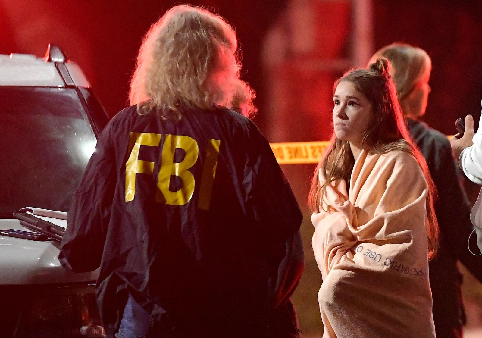 "An FBI agent talks to a potential witness as they stand near the scene Thursday, Nov. 8, 2018, in Thousand Oaks, Calif. where a gunman opened fire Wednesday inside a country dance bar crowded with hundreds of people on ""college night."" (AP Photo/Mark J. Terrill)"