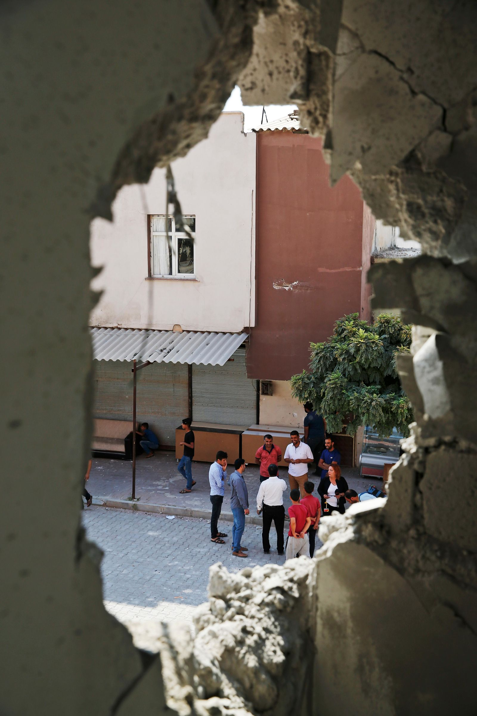 People are seen through a hole in a building damaged by a mortar fired from inside Syria, in Akcakale, Sanliurfa province, southeastern Turkey, Sunday, Oct. 13, 2019.{ } (AP Photo/Lefteris Pitarakis)