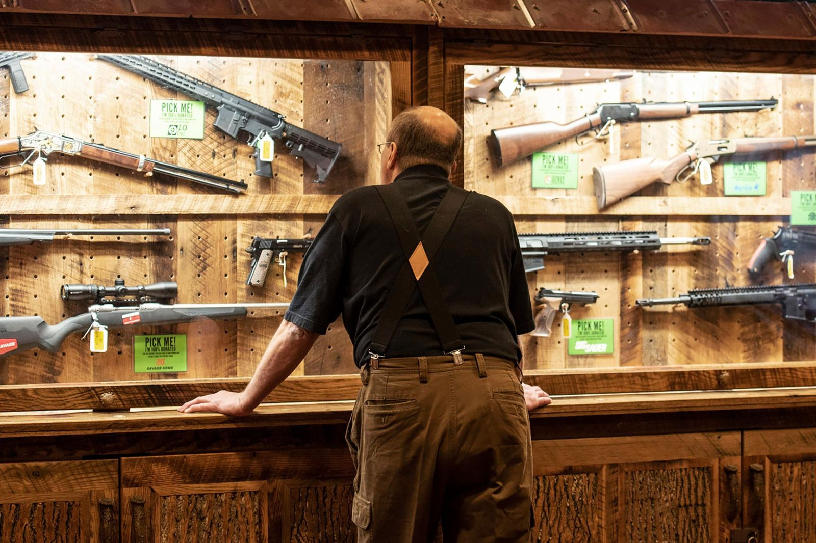 FILE - In this April 25, 2019, file photo, a man looks at cases of firearms in the halls of the Indianapolis Convention Center where the National Rifle Association will be holding its 148th annual meeting in Indianapolis. (AP Photo/Lisa Marie Pane, File)