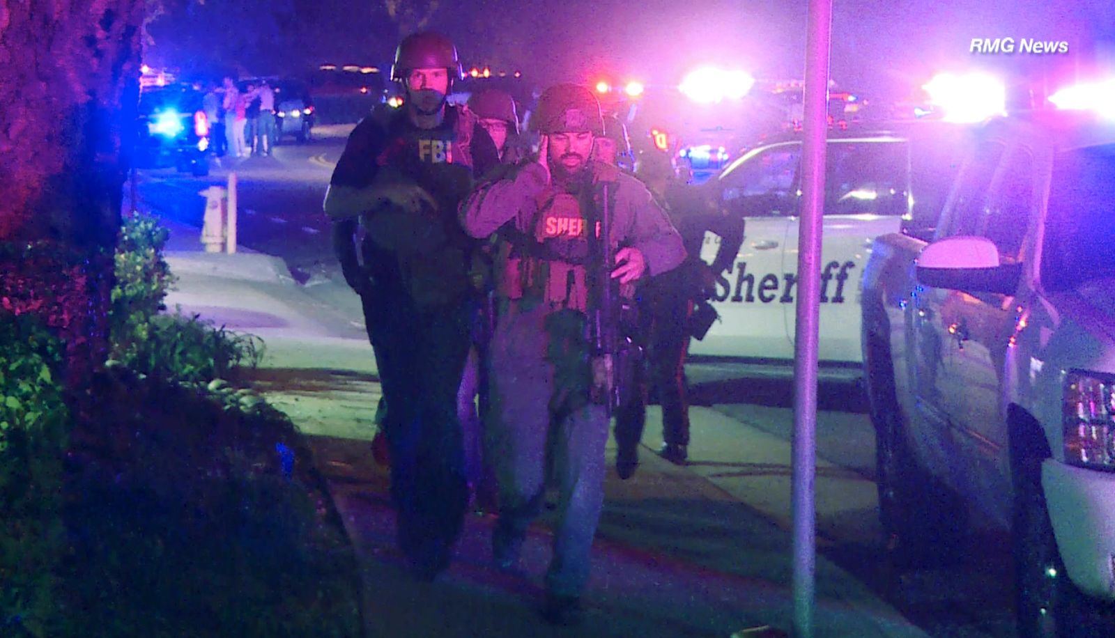 In this image taken from video police officers and FBI agents run at the scene of a shooting, early Thursday morning, Nov. 8, 2018, in Thousand Oaks, Calif.{ } (RMG News via AP)