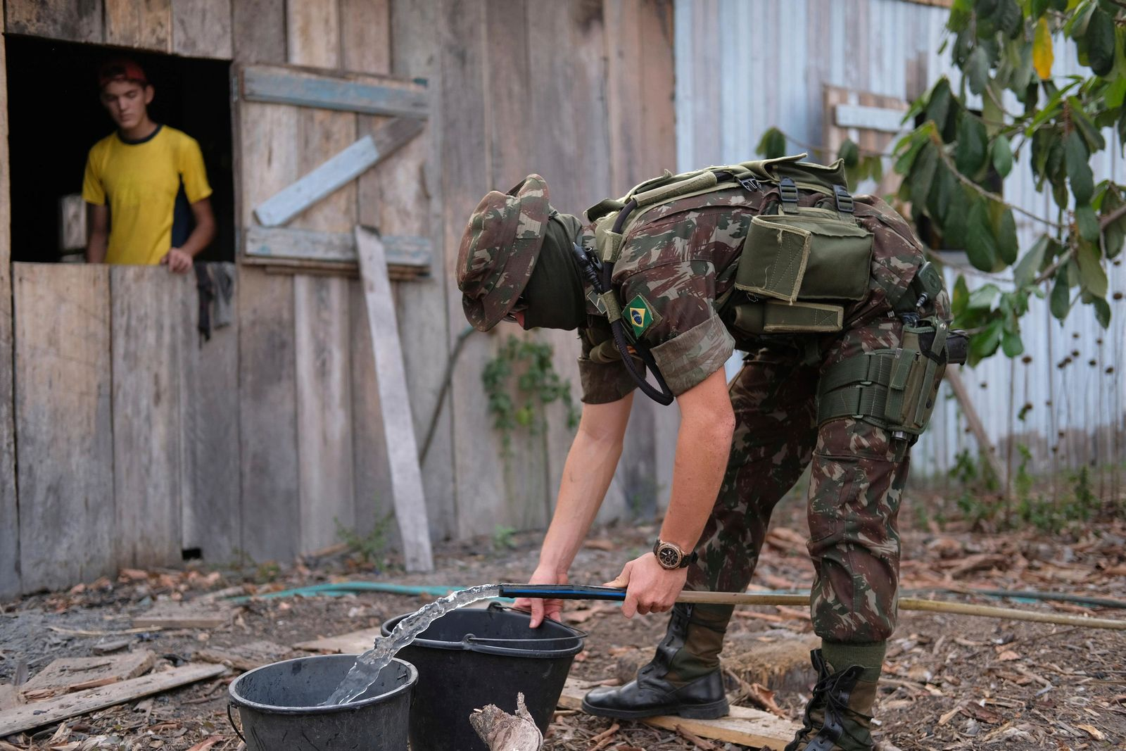 A member of Brazil's 17th brigade of jungle infantry fills up buckets with water at a property owned by the family of Eric Raauwendaal, left, at Jacunda National Forest, in the Amazonian state of Rondonia, Brazil, Thursday, August 29, 2019. A record number of fires in the Amazon has prompted an environmental crisis and a global outcry. (AP Photo/Luis Andres Henao)