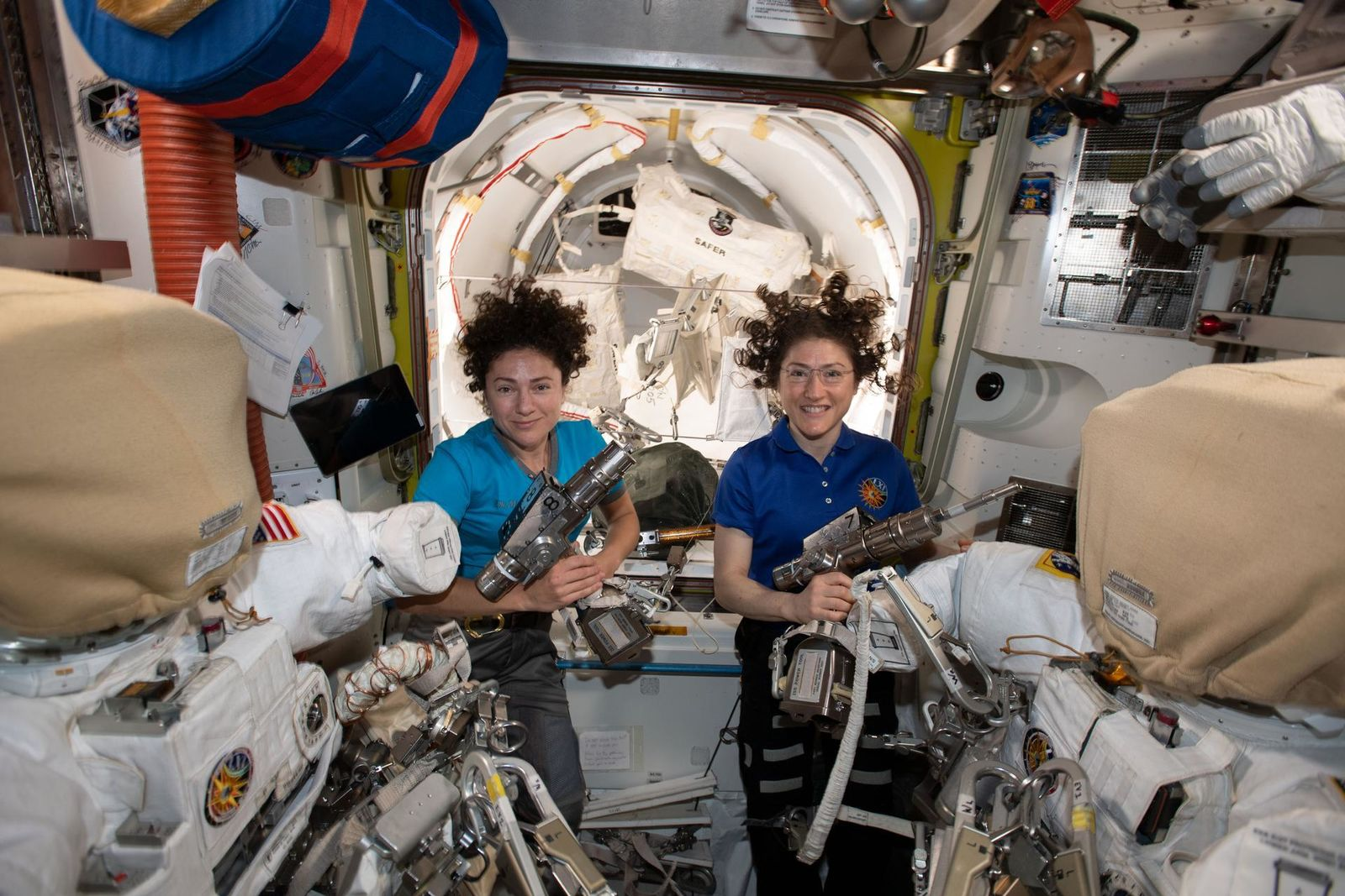 NASA astronauts Jessica Meir (left) and Christina Koch are inside the Quest airlock preparing the U.S. spacesuits and tools they will use on their first spacewalk together. The Expedition 61 flight engineers are holding the pistol grip tools they will use to swap out a failed power controller, also known as a battery charge-discharge unit, that regulates the charge to batteries that collect and distribute power to the International Space Station. (NASA)