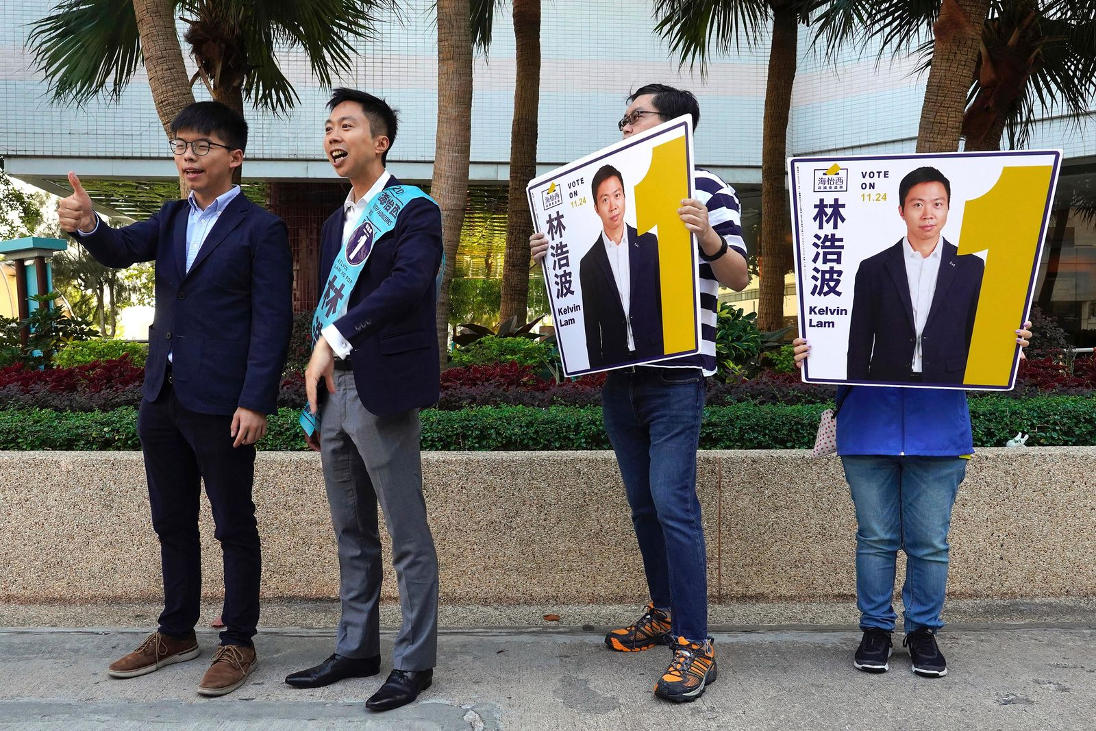 "Pro-democracy activist Joshua Wong, left, campaigns with local election candidate Kelvin Lam, second from left, in Hong Kong, Saturday, Nov. 23, 2019. Chanting ""No more tear gas,"" dozens of Hong Kong families with young children are marching to oppose the government's handling of protests on the eve of keenly contested local elections. (AP Photo/Vincent Yu)"