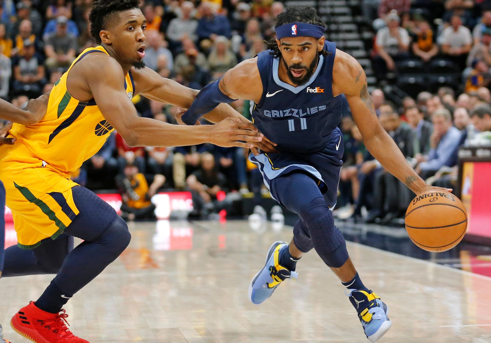 Memphis Grizzlies guard Mike Conley (11) drives around Utah Jazz guard Donovan Mitchell, left, in the first half of an NBA basketball game Monday, Oct. 22, 2018, in Salt Lake City. (AP Photo/Rick Bowmer)