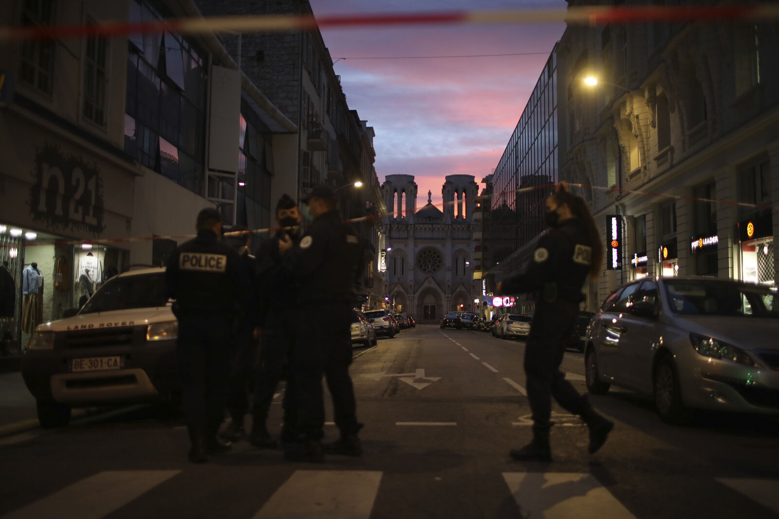 FILE- Police work behind a restricted zone near the Notre Dame church in Nice, southern France, after a knife attack took place on Thursday, Oct. 29, 2020. (AP Photo/Daniel Cole)