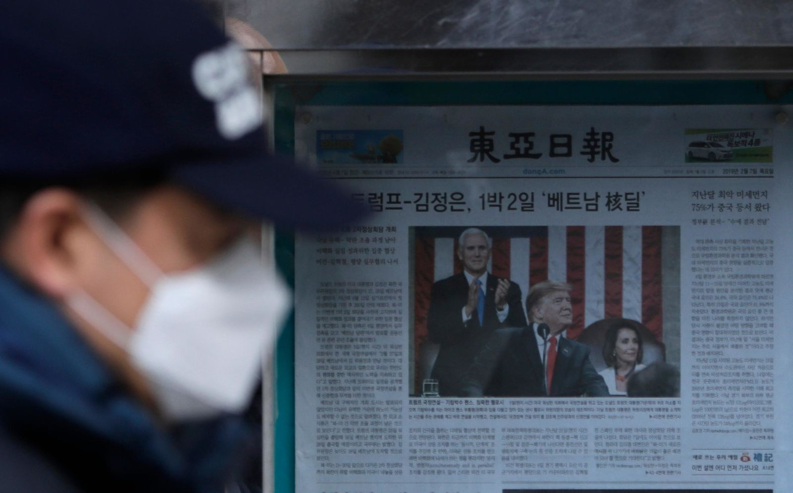 A man walks by a newspaper reporting U.S. President Donald Trump delivering his State of the Union address, displayed on a street in Seoul, South Korea, Thursday, Feb. 7, 2019. (AP Photo/Lee Jin-man)