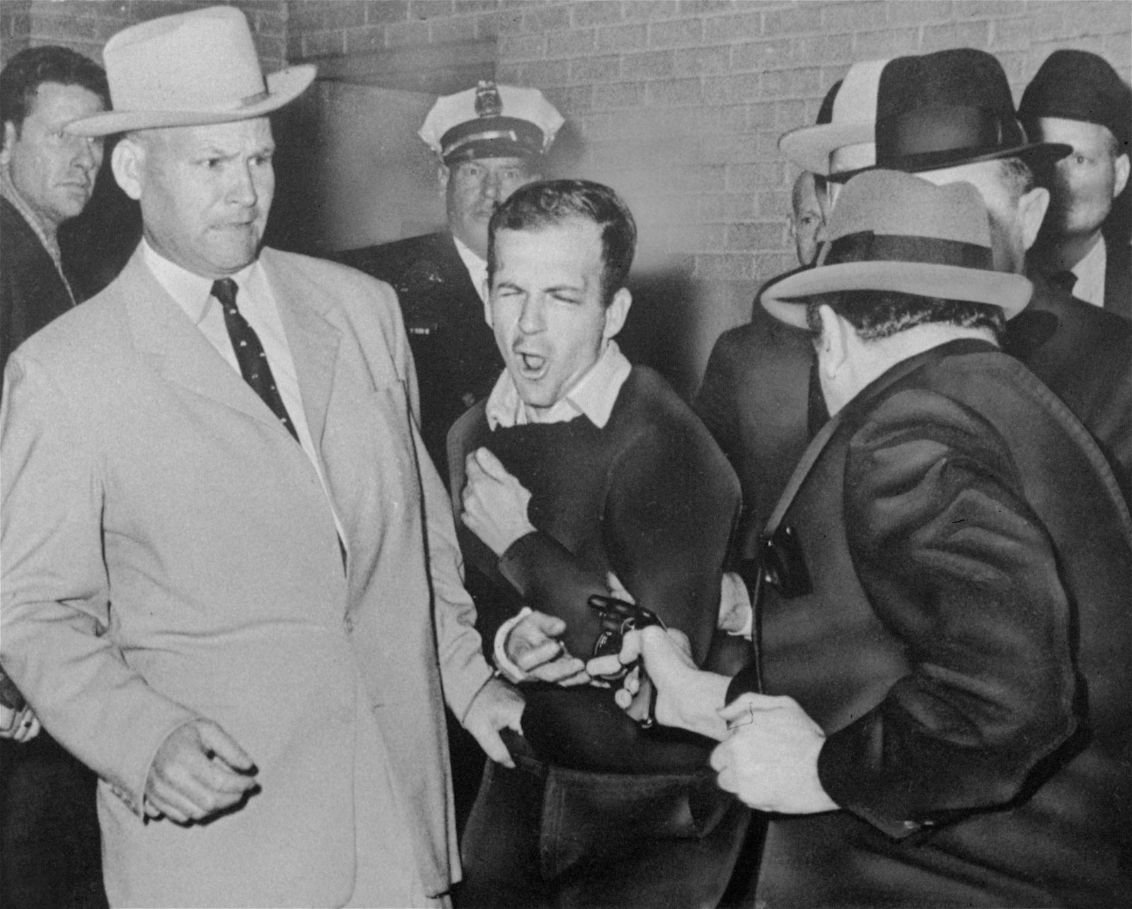 FILE - In this Nov. 24, 1963 file photo, Lee Harvey Oswald reacts as Dallas night club owner Jack Ruby, foreground, shoots at him from point blank range in a corridor of Dallas police headquarters At left is Detective Jim Leavelle. The longtime Dallas lawman who was captured in one of history's most iconic photographs as he escorted President John F. Kennedy's assassin moments before he was fatally shot, has died on Thursday, Aug. 29, 2019. He was 99. (Bob Jackson/Dallas Times-Herald via AP)