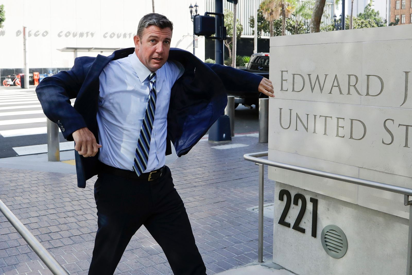 U.S. Rep. Duncan Hunter pulls on his coat as he arrives for an arraignment hearing Thursday, Aug. 23, 2018, in San Diego. Hunter and his wife were indicted on federal charges that they used more than $250,000 in campaign funds for personal expenses that ranged from groceries to golf trips and lied about it in federal filings, prosecutors said. (AP Photo/Gregory Bull)