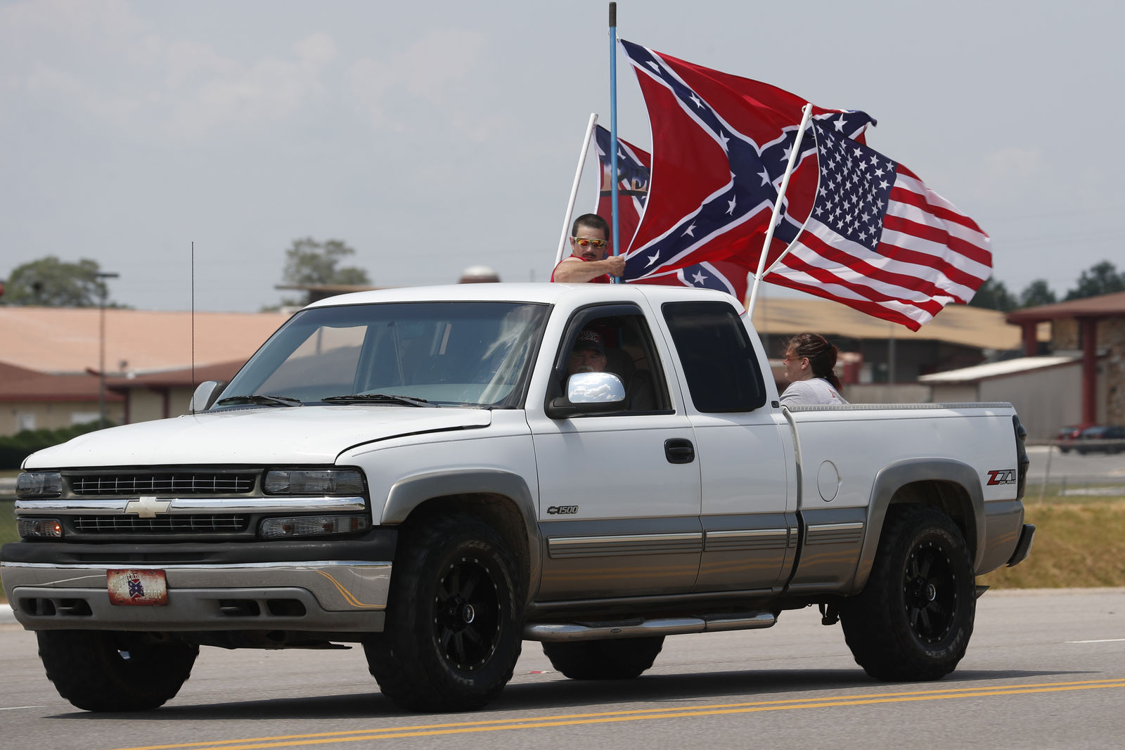 FILE - In this  June 21, 2020, file photo, race fans fly Confederate battle flags and a United States flag as they drive by Talladega Superspeedway prior to a NASCAR Cup Series auto race in Talladega, Ala. (AP Photo/John Bazemore, File)