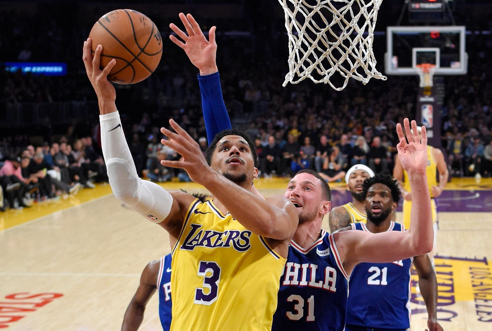 FILE - In this Jan. 29, 2019, file photo, Los Angeles Lakers guard Josh Hart, left, shoots as Philadelphia 76ers forward Mike Muscala defends during the second half of an NBA basketball game in Los Angeles. Two people familiar with the situation say the New Orleans Pelicans have agreed to trade six-time All-Star Anthony Davis to the Lakers for point guard Lonzo Ball, forward Brandon Ingram, Hart and three first-round draft choices. The people spoke to The Associated Press on condition of anonymity because the trade cannot become official until the new league year begins July 6. ESPN first reported the trade. (AP Photo/Mark J. Terrill, File)