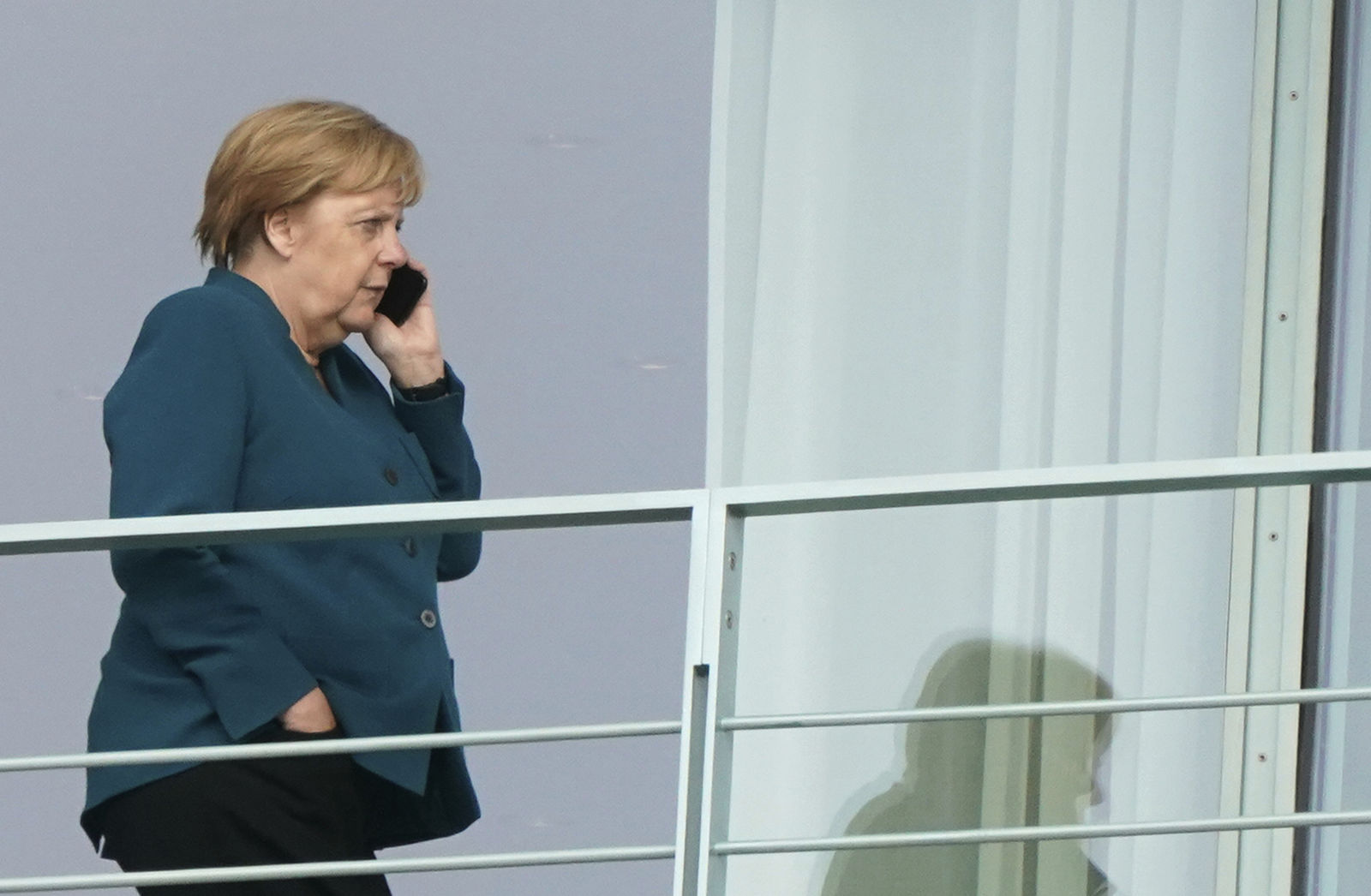 German Chancellor Angela Merkel makes a telephone call on a balcony of the Chacellery in Berlin, Germany, Friday, Sept. 20, 2019.{ } (Kay Nietfeld/dpa via AP)