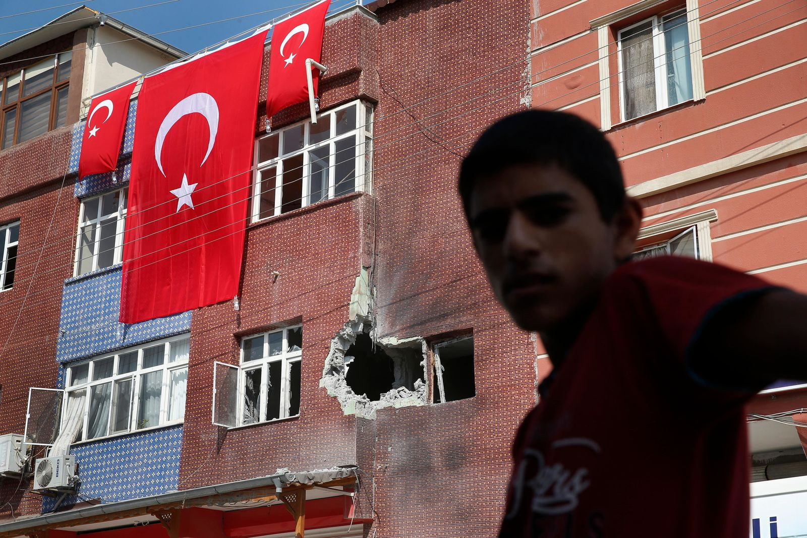 A child stands across from a building damaged by a mortar fired from inside Syra, in Akcakale, Sanliurfa province, southeastern Turkey, Sunday, Oct. 13, 2019. (AP Photo/Lefteris Pitarakis)