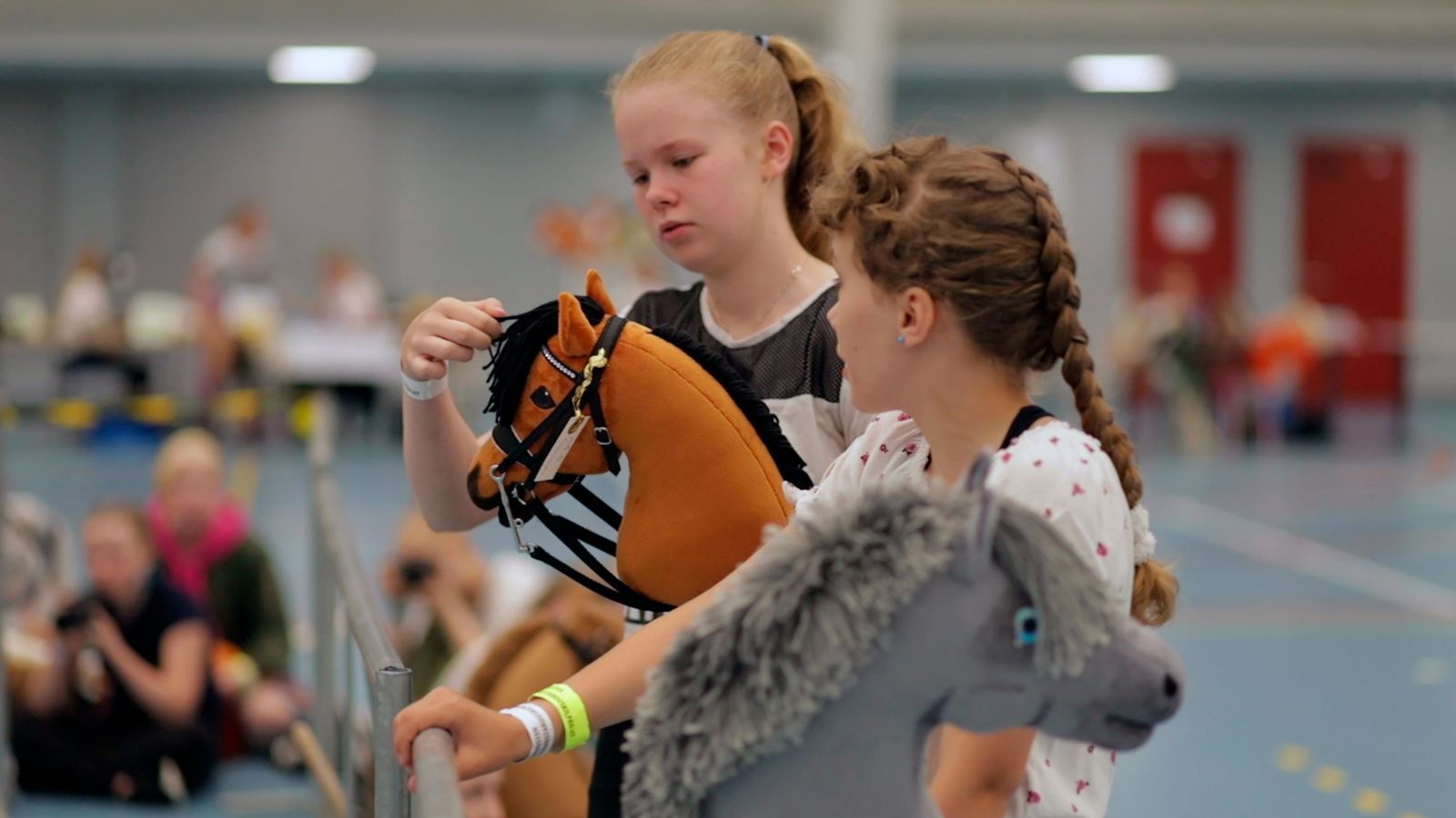 Young hobby horse competitors care for their toy horses in Seinajoki, Finland, on Saturday, June 15, 2019. More than 400 hobby horse enthusiasts took part in Finland's 8th Hobby Horse championships, competing on stylish toy horses in various events inspired by real equestrian events. (AP Photo/from APTN Video)