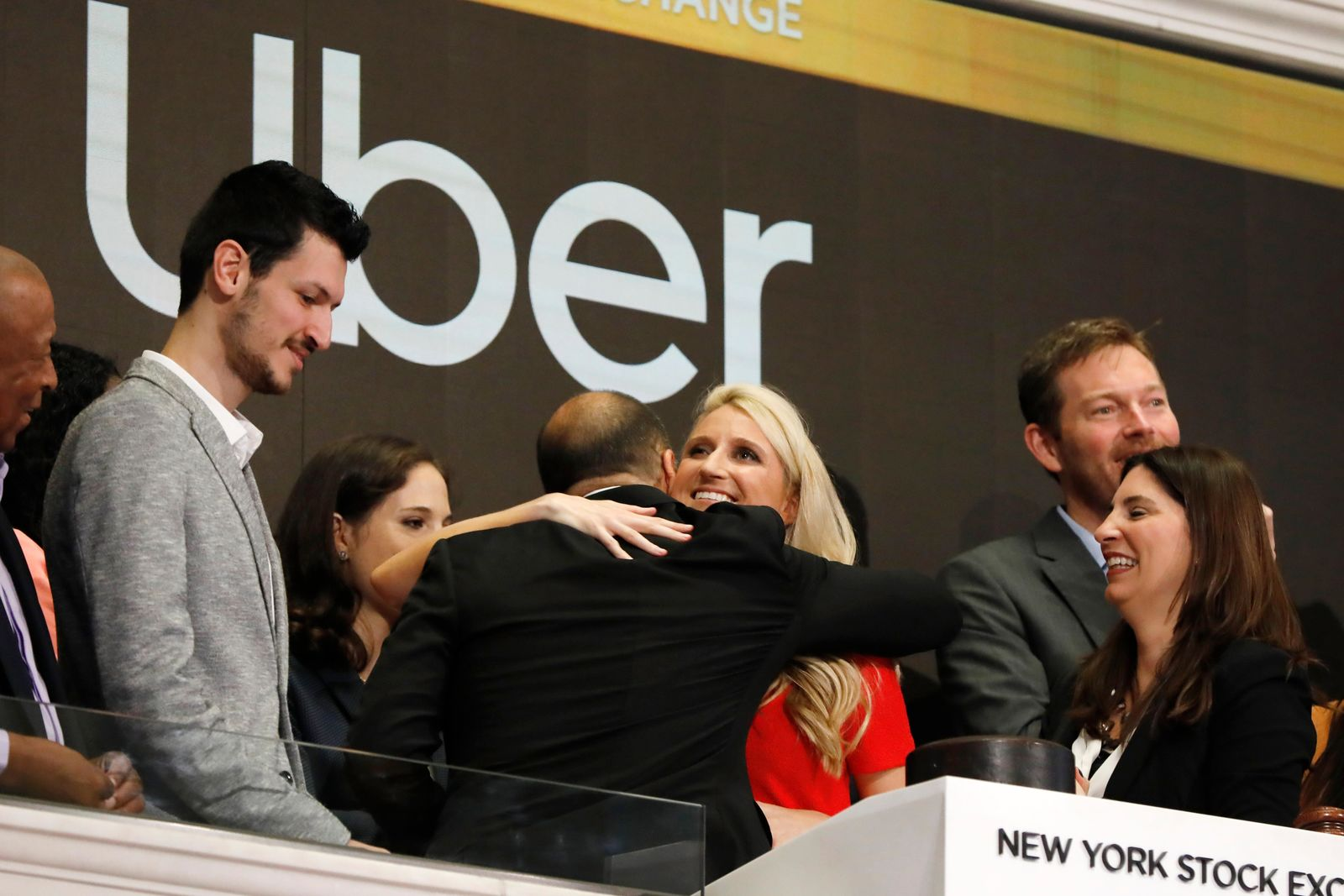 Uber CEO Dara Khosrowshahi, back to camera, hugs company employee Austin Geidt at the opening bell ceremony at the New York Stock Exchange, as his company makes its initial public offering, Friday, May 10, 2019. (AP Photo/Richard Drew)