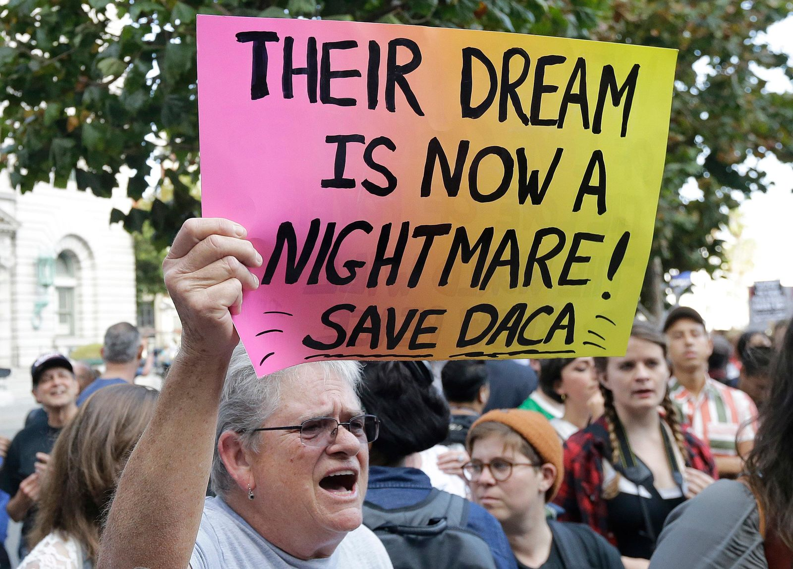 FILE - In this Sept. 15, 2017, file photo, Judy Weatherly, a supporter of the Deferred Action for Childhood Arrivals (DACA) holds up a sign during a protest outside of the Federal Building in San Francisco. (AP Photo/Jeff Chiu, File)