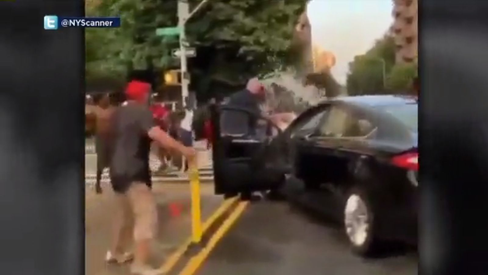 This screenshot of a social media video shows police officers in Harlem being hit with an empty bucket and doused with water as they make an arrest. (Image: WCBS via CNN Newsource)