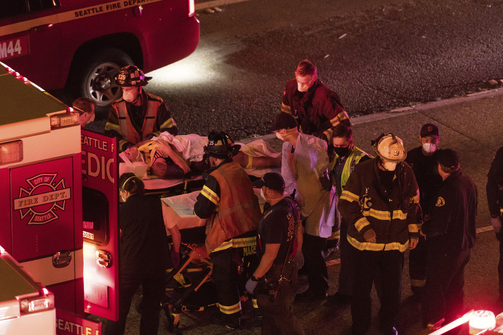 Emergency workers bring an injured person to an ambulance after a driver sped through a protest-related closure on the Interstate 5 freeway in Seattle, authorities said early Saturday, July 4, 2020. (James Anderson via AP)